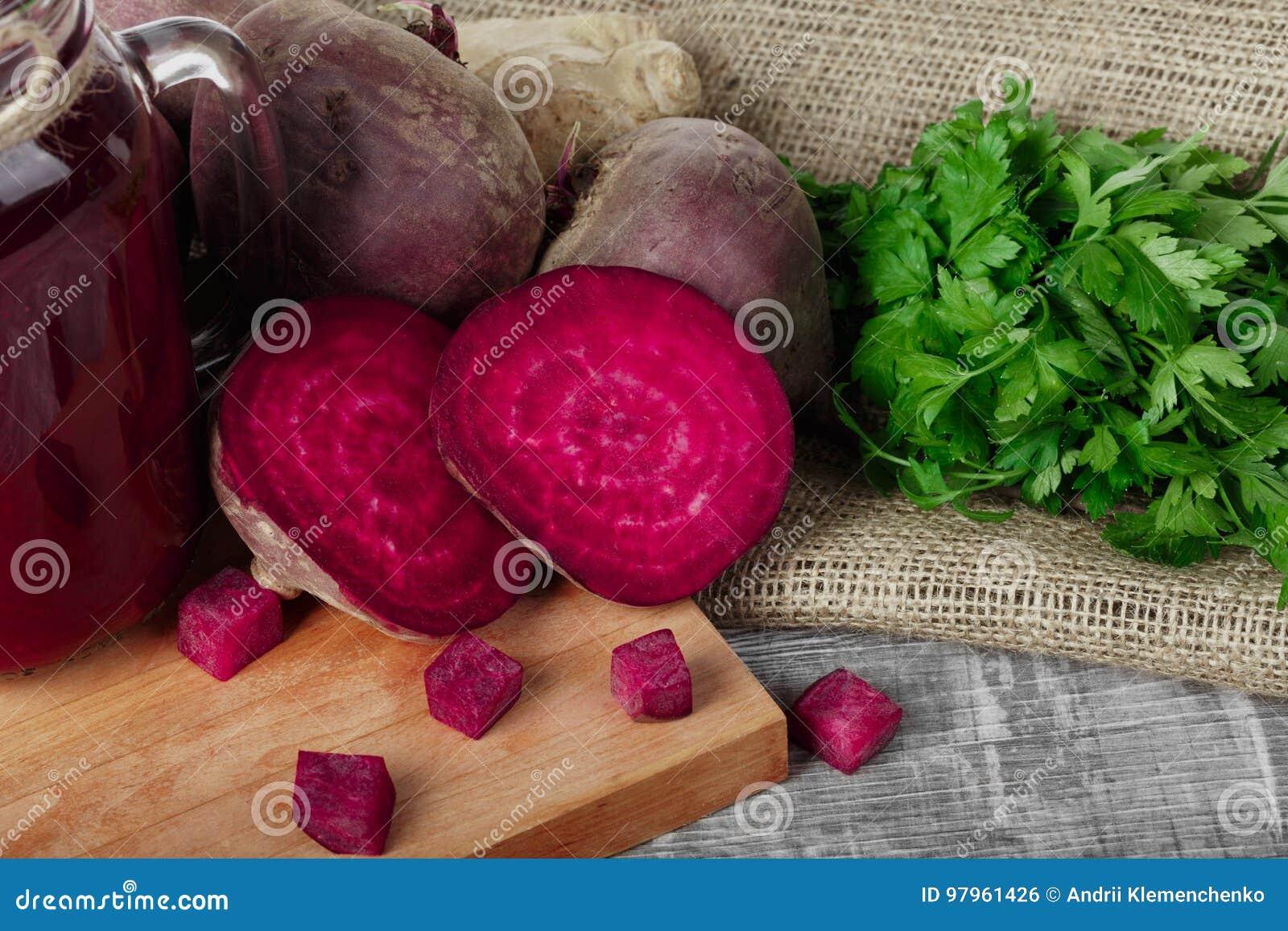 Beterrabas, salsa e bebida inteiras e cortadas em uma placa de corte e em um fundo de madeira Vegetais do jardim