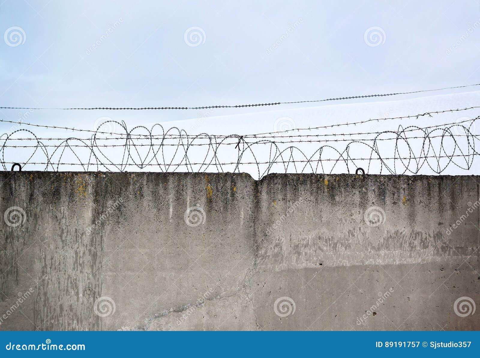 Betonmauer, gegen den Hintergrund des Stacheldrahts, das Konzept