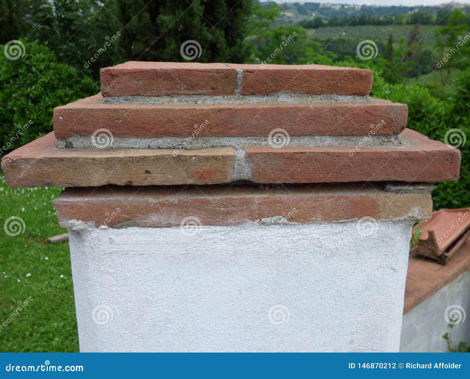 Betonpfosten am Ende einer Wand mit einer Kappe des roten Backsteins