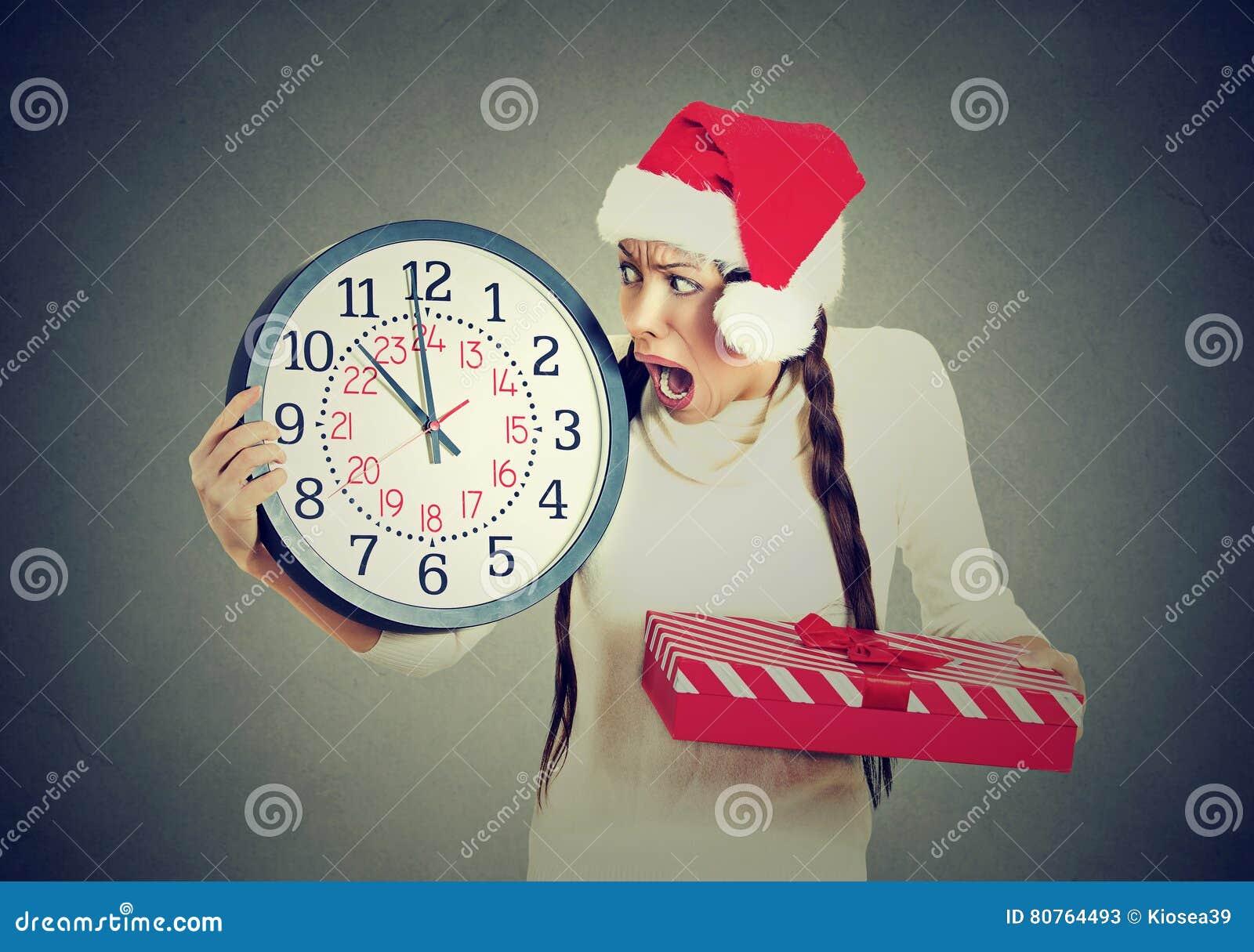 Betonte in Eile Frau, die Weihnachtsmann-Hut hält Uhrgeschenkbox trägt