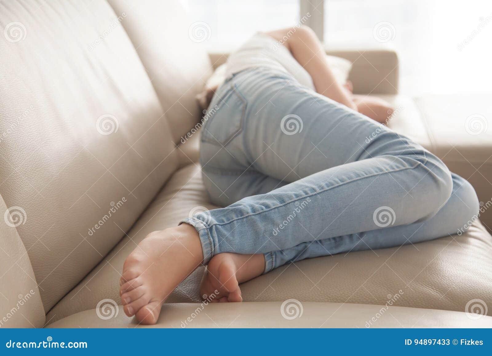 Betontes Lügenumkippen der Frau auf Sofa zu Hause