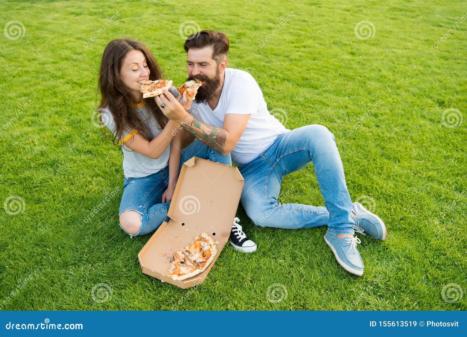 Betr?germahlzeit Verbinden Sie das Essen der Pizza, die auf grünem Rasen sich entspannt Schnellimbisslieferung Bärtiger Mann und
