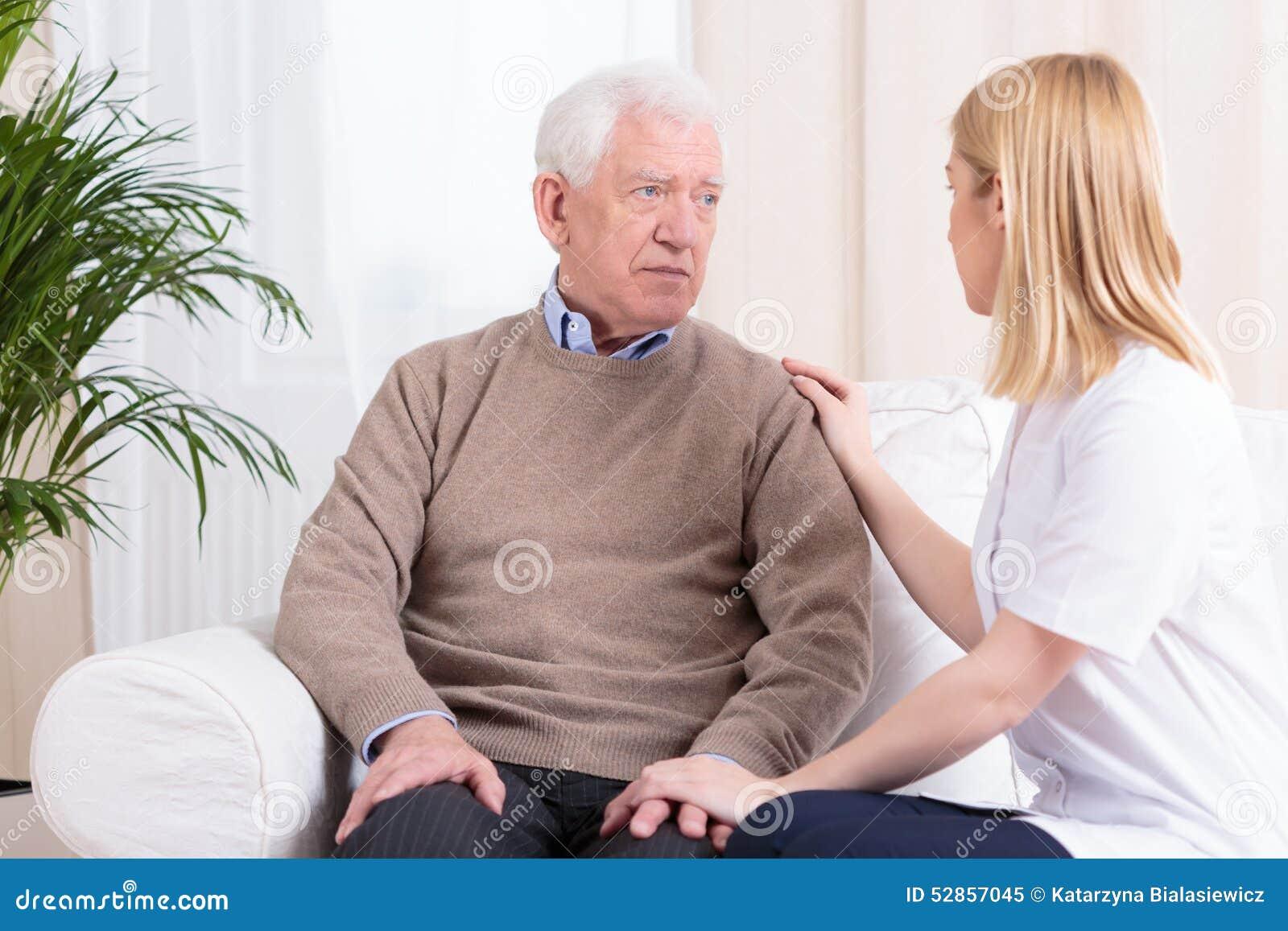 Betreuer, der älteren Mann stützt