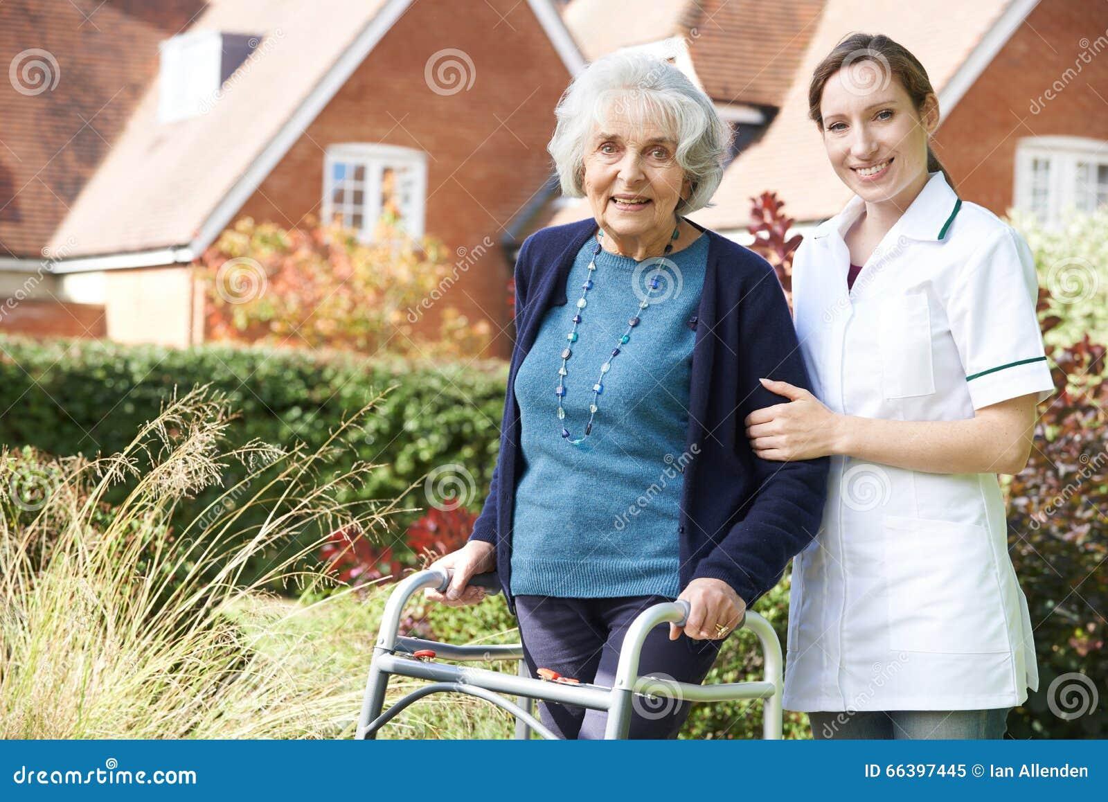 Betreuer, welche älterer Frau hilft, in Garten unter Verwendung des gehenden Rahmens zu gehen