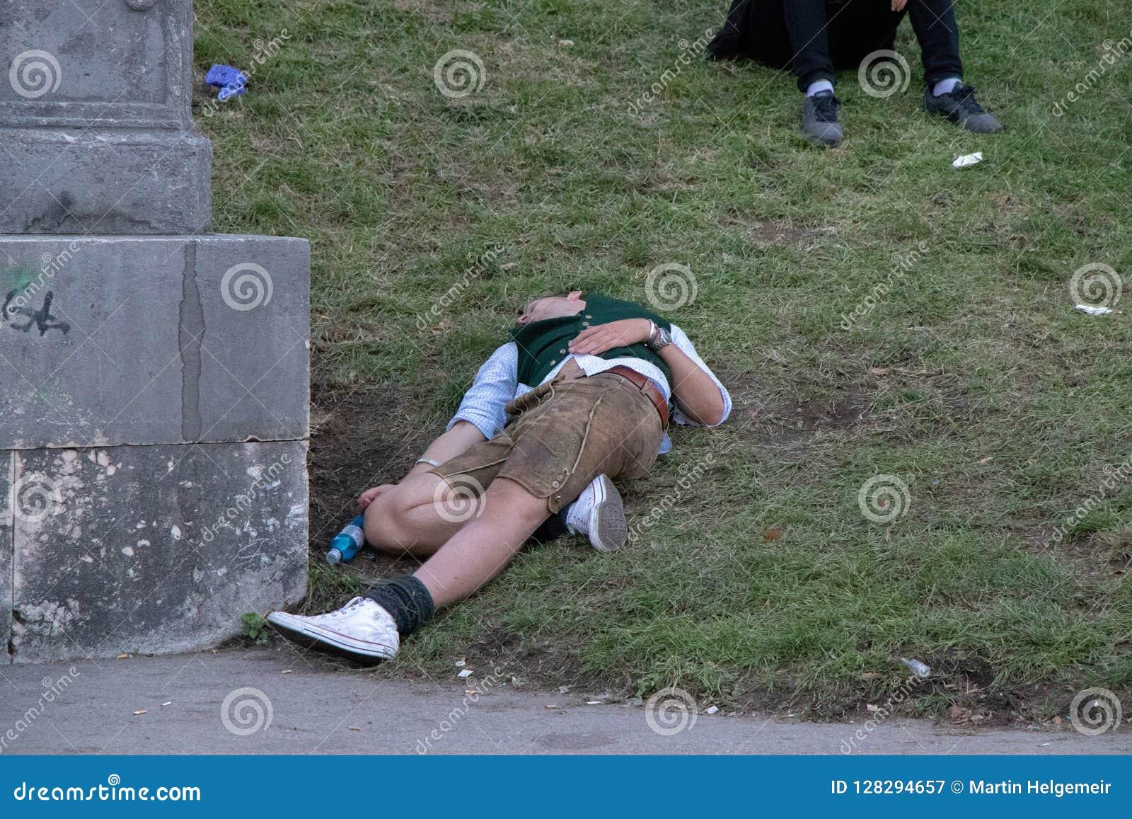 Betrunkener Mann, der in dem Bayern, Oktoberfest, München schläft