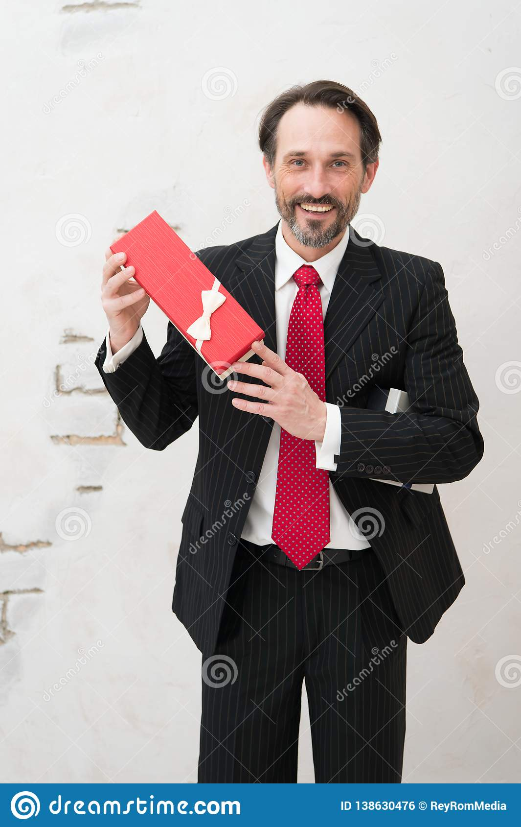 Lighthearted charismatic businessman holding a present in red box