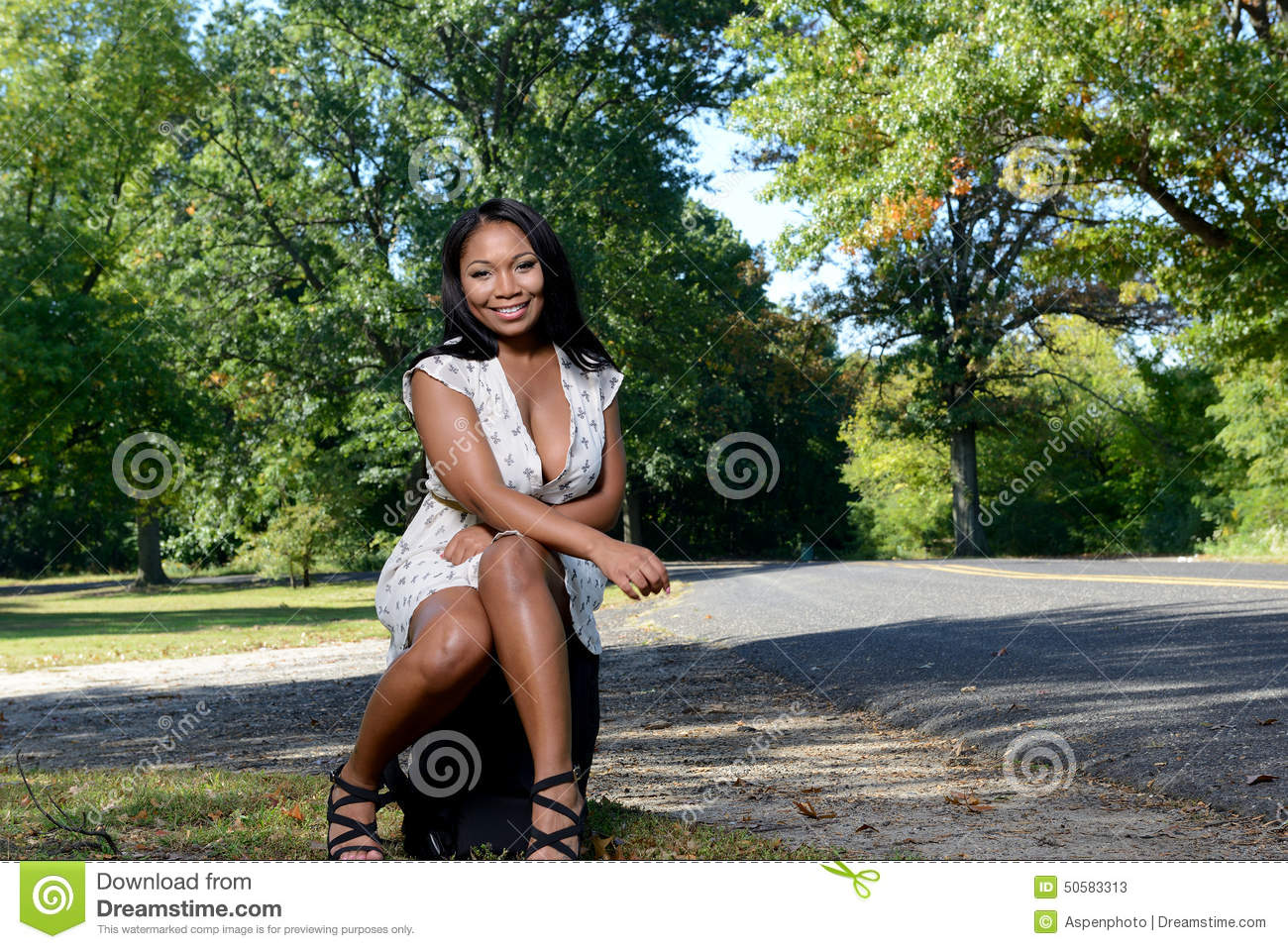 Beuatiful African American woman sitting next to road