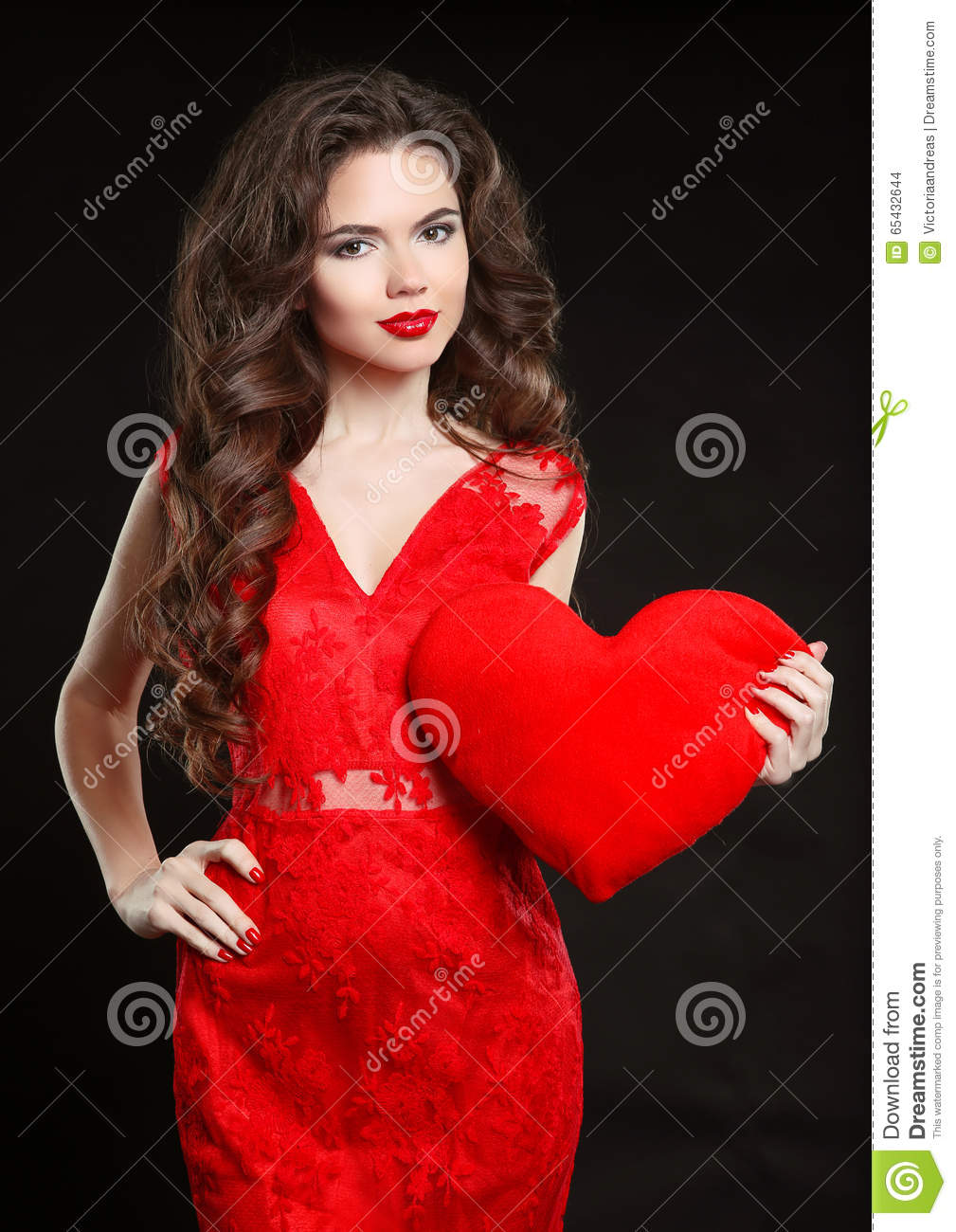 Beuatiful girl with valentine heart wearing in red dress