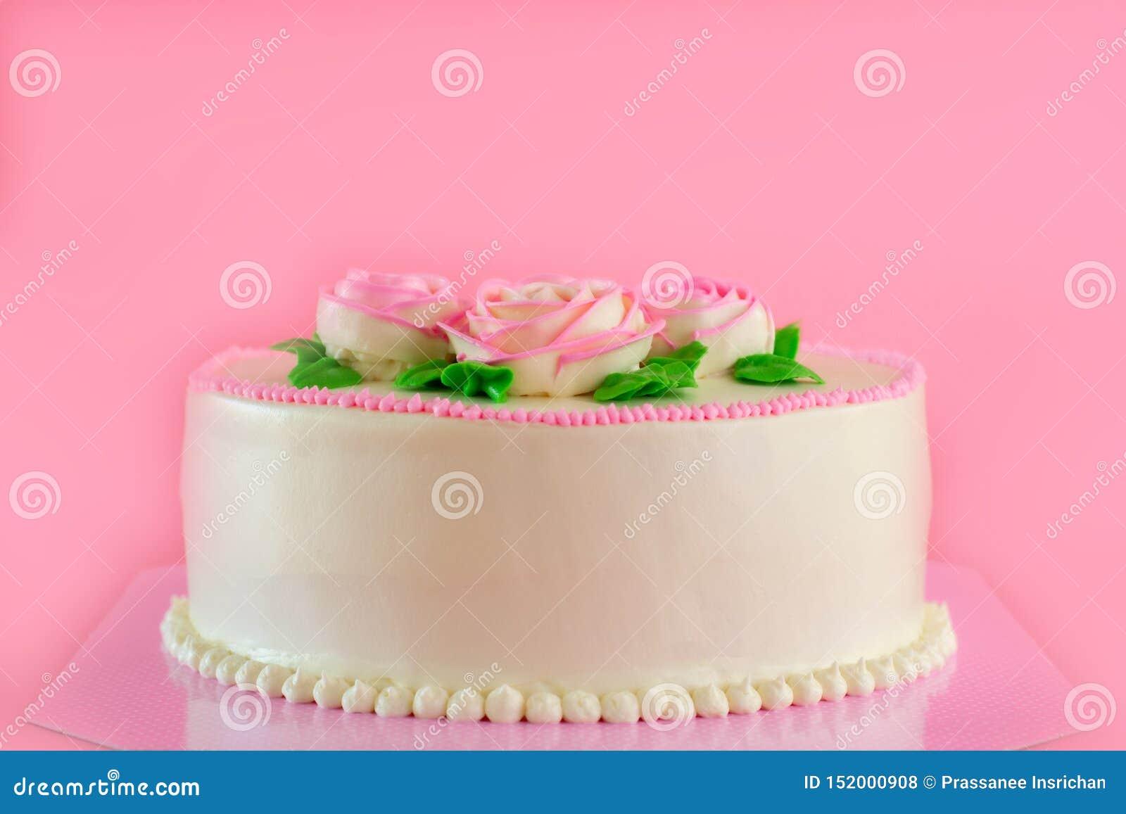Beurrez la crème du gâteau d étang de vanille d oo décoré par roses roses sur le fond rose avec l espace de copie servi en fête d