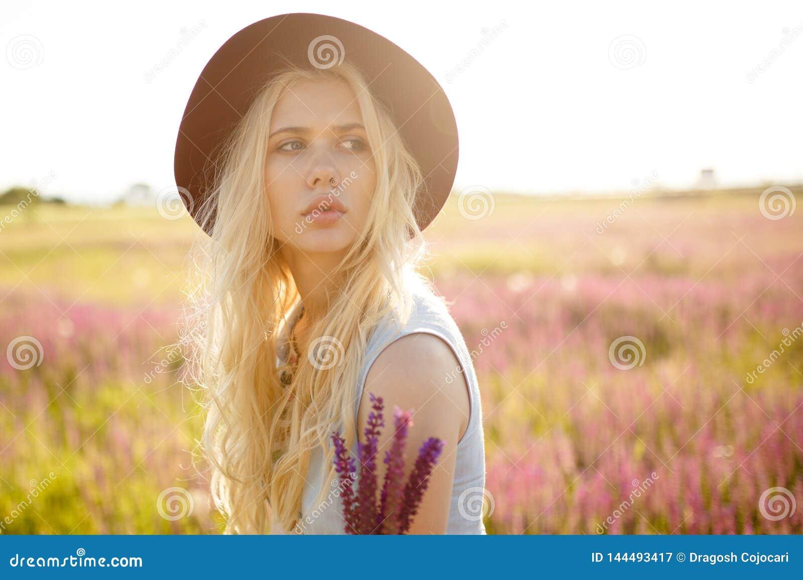 Beutyportret van het schitterende blondemeisje dragen in hoed buiten het stellen, dat op een bloemengebied, op zonsondergangachte