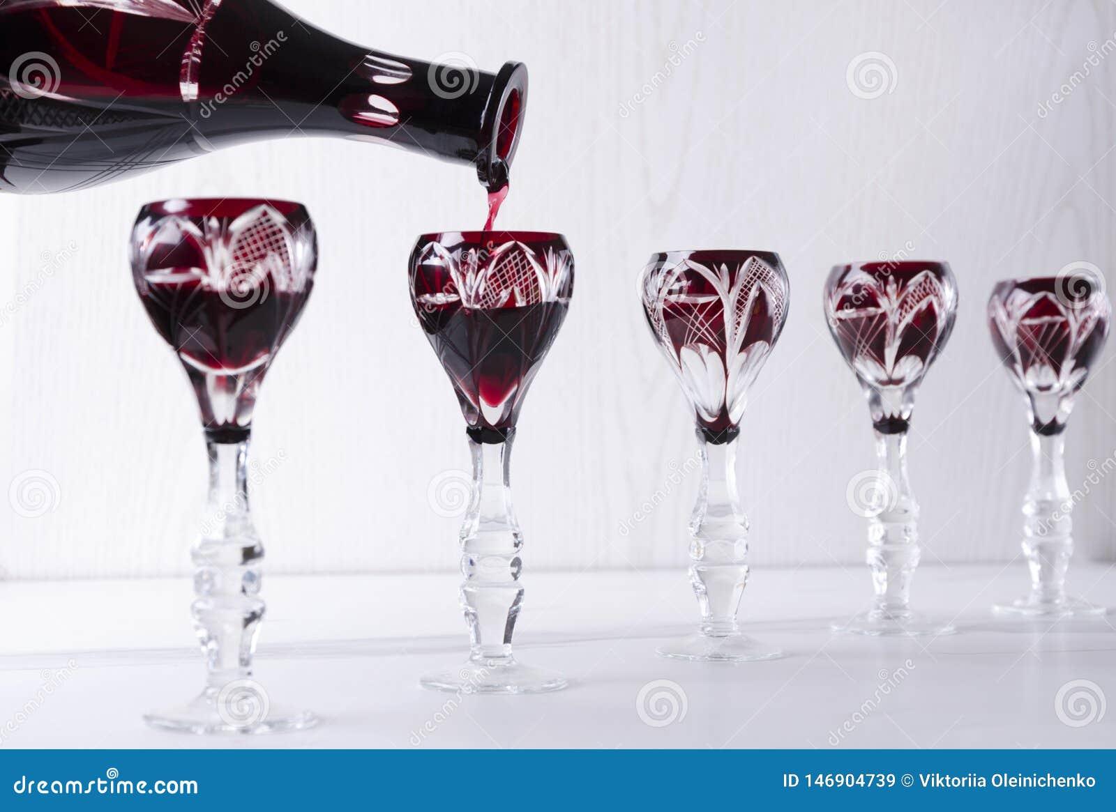 Bevanda alcolica amara rossa di versamento nei vetri d annata Concetto della cena del buffet