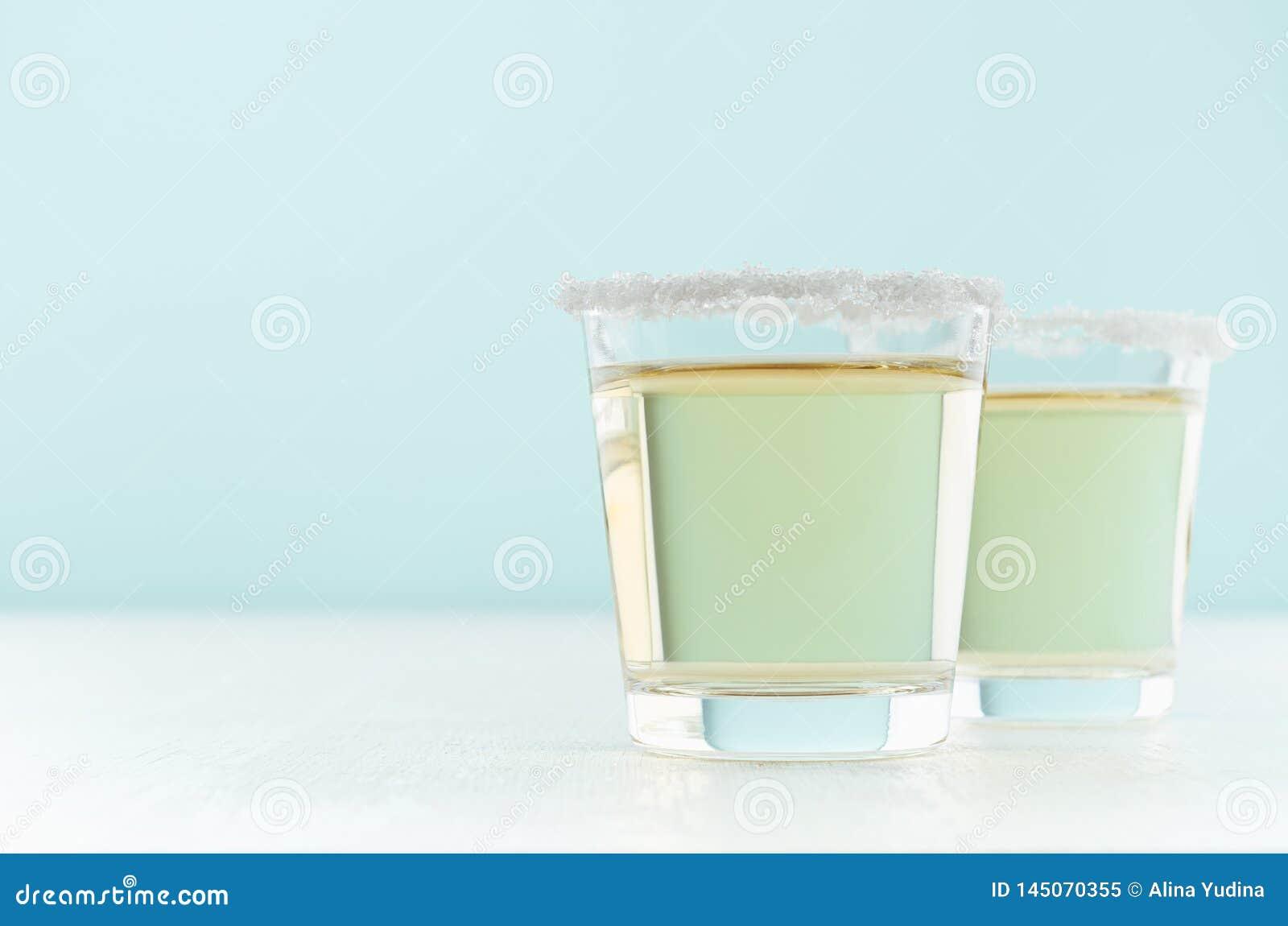 Bevanda gialla dell alcool fresco tropicale - tequila dorata in due vetri sparati con l orlo di sale nella cucina pastello elegan