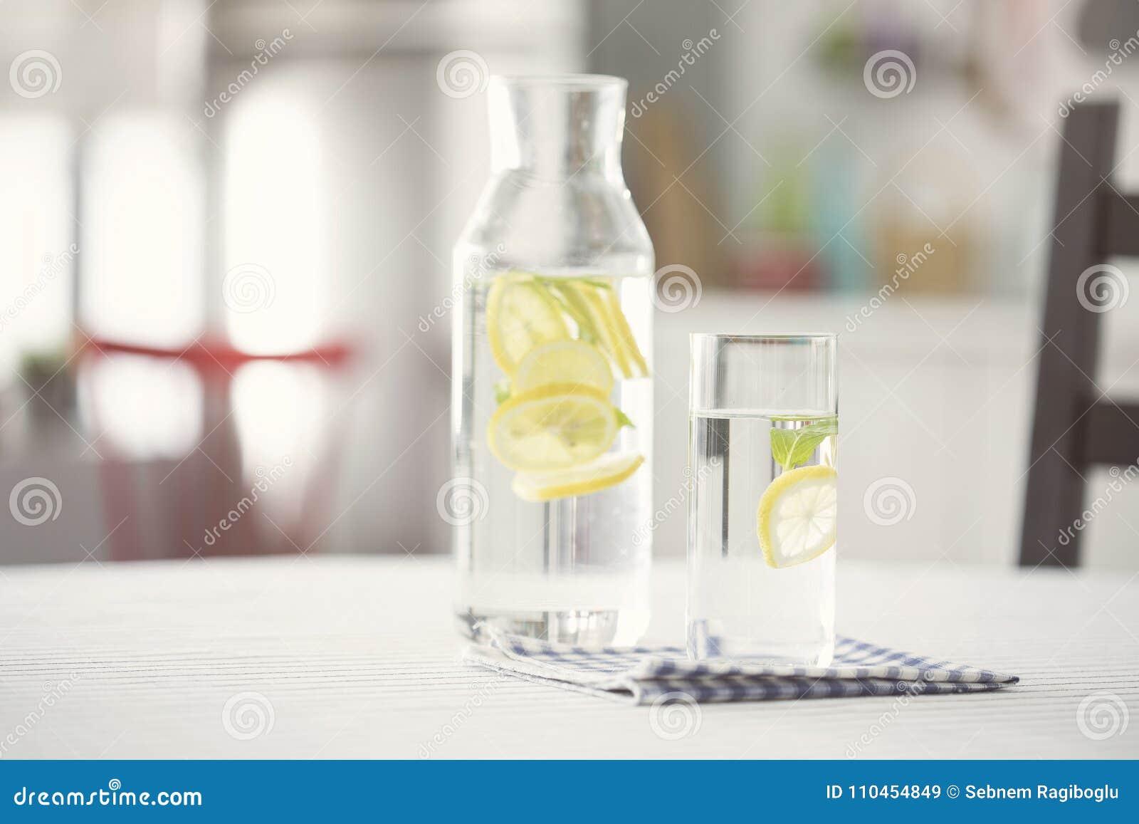 Bevattna bottel och exponeringsglas av vatten med citronen i kök