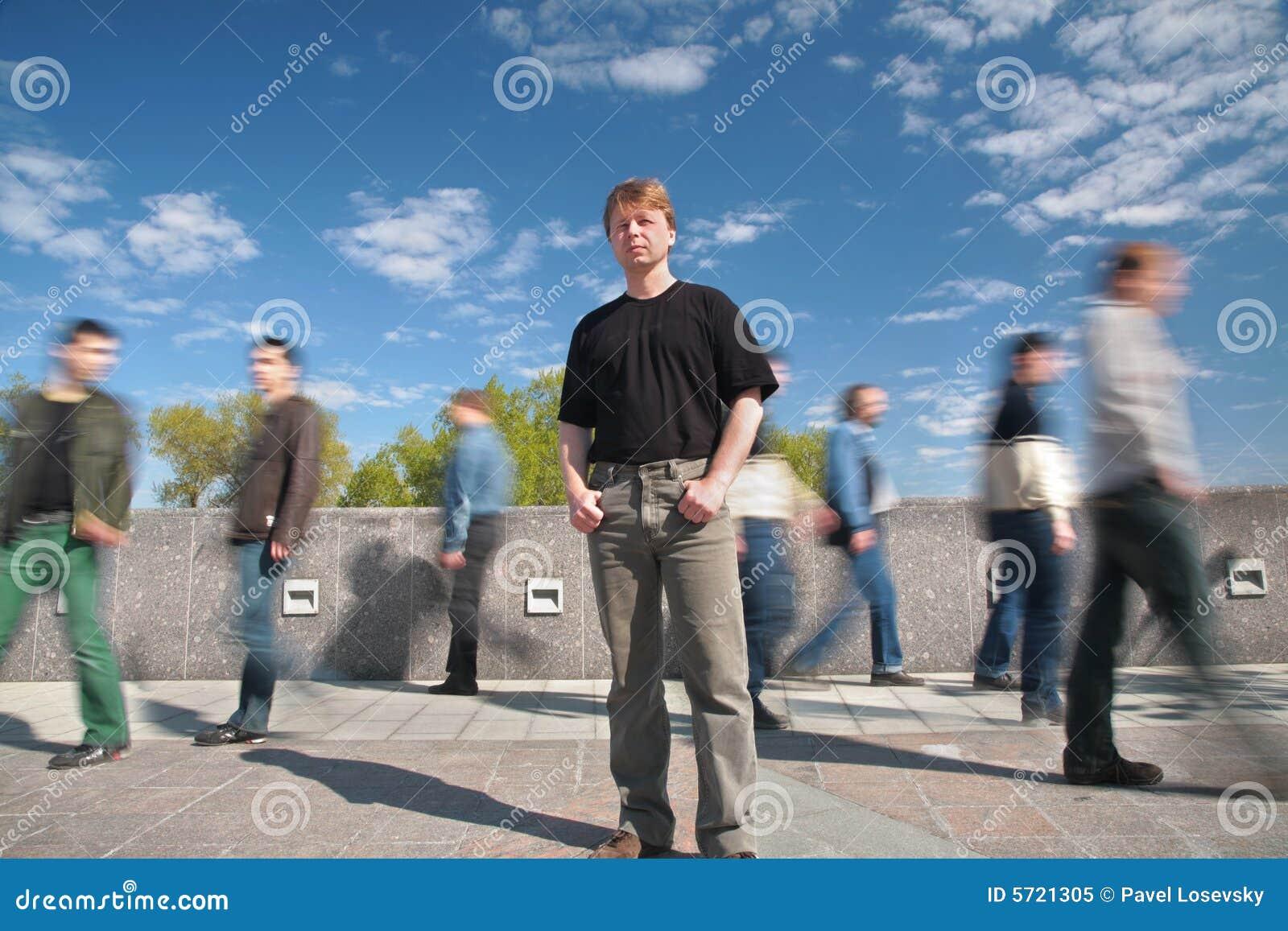 Bevindende mens onder bewegende voetgangers