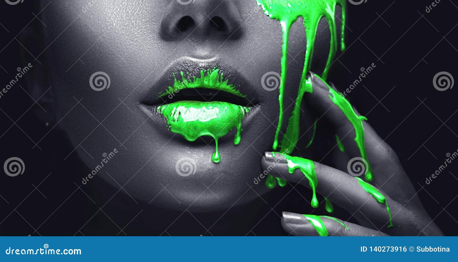 Bevlekt de neon groene verf druppels van de gezichtslippen en hand, groene vloeibare dalingen op de mond van het mooie modelmeisj