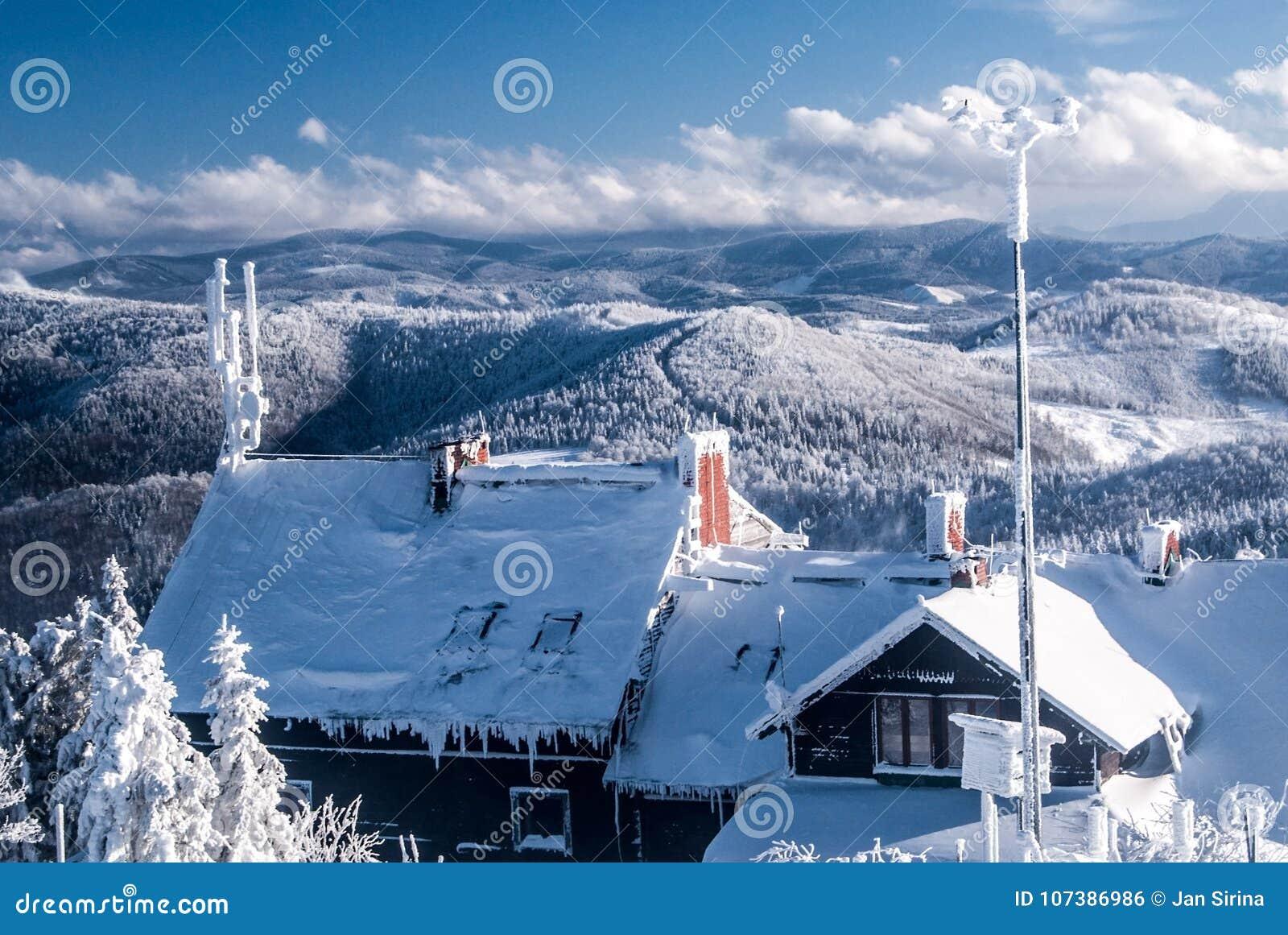 Bevriezende de winterdag op de heuvel van Wielka Racza in de bergen van Beskid Zywiecki met chalet en heuvels op de achtergrond