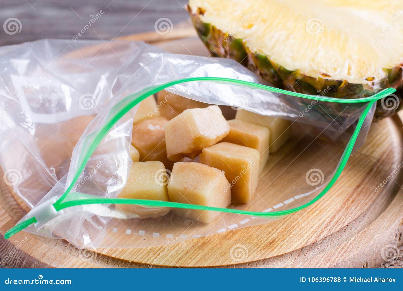 Bevroren ananaskubussen in een zak van hakbord