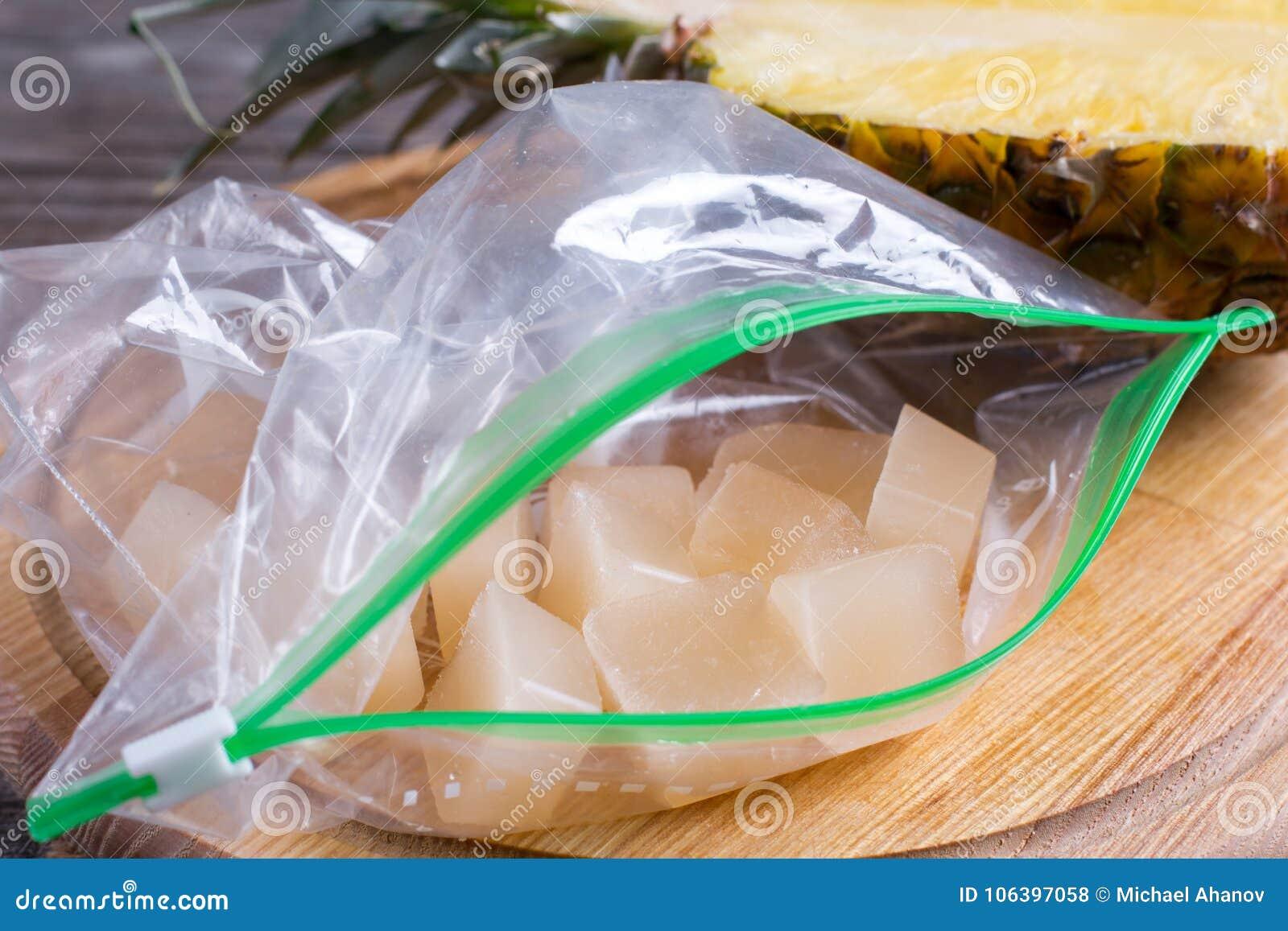 Bevroren ananassapkubussen in een zak op een houten lijst