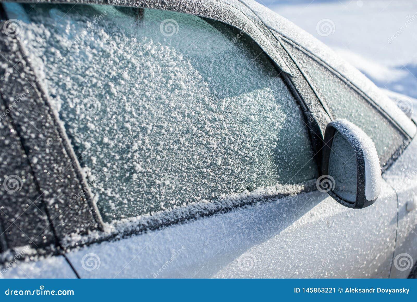 Bevroren automobieldieglas met ijs wordt behandeld