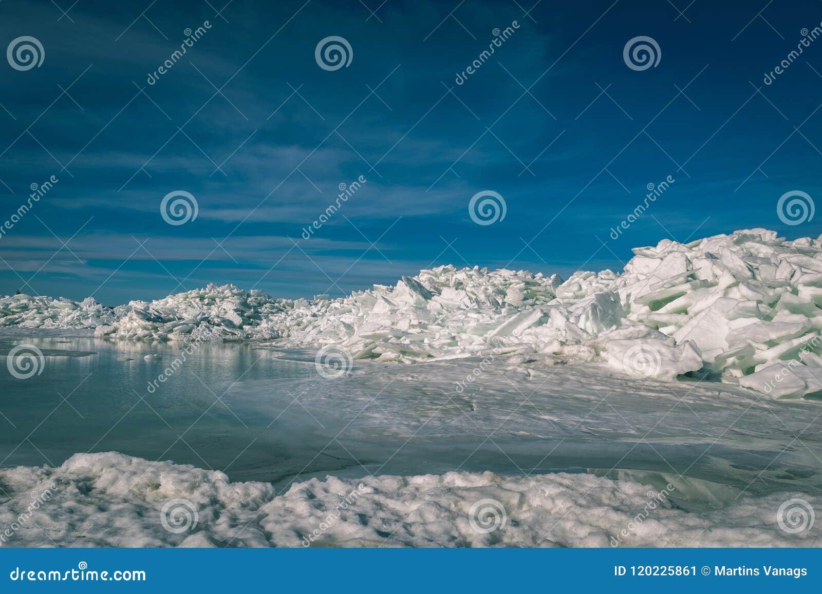 Bevroren die meer met stapel van ijsijsschollen en blauwe hemel wordt behandeld - vinta