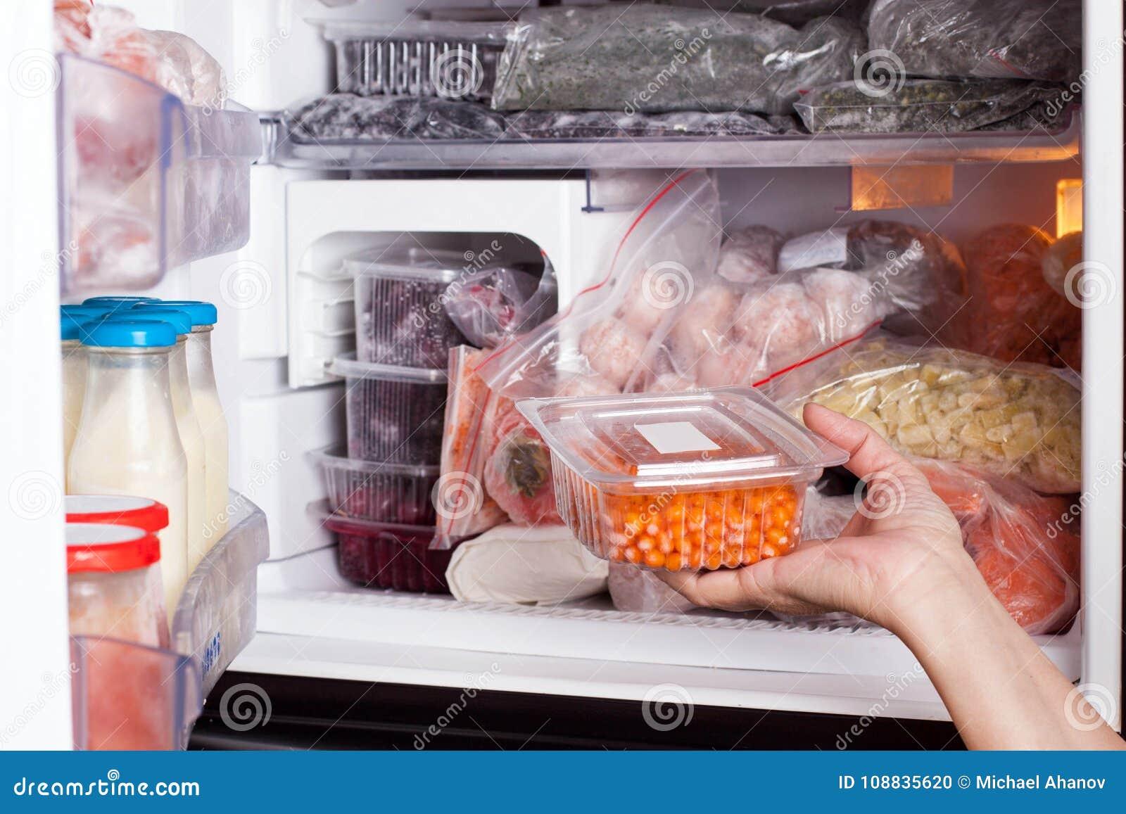 Bevroren voedsel in de ijskast Groenten op de diepvriezerplanken Voorraden van maaltijd voor de winter