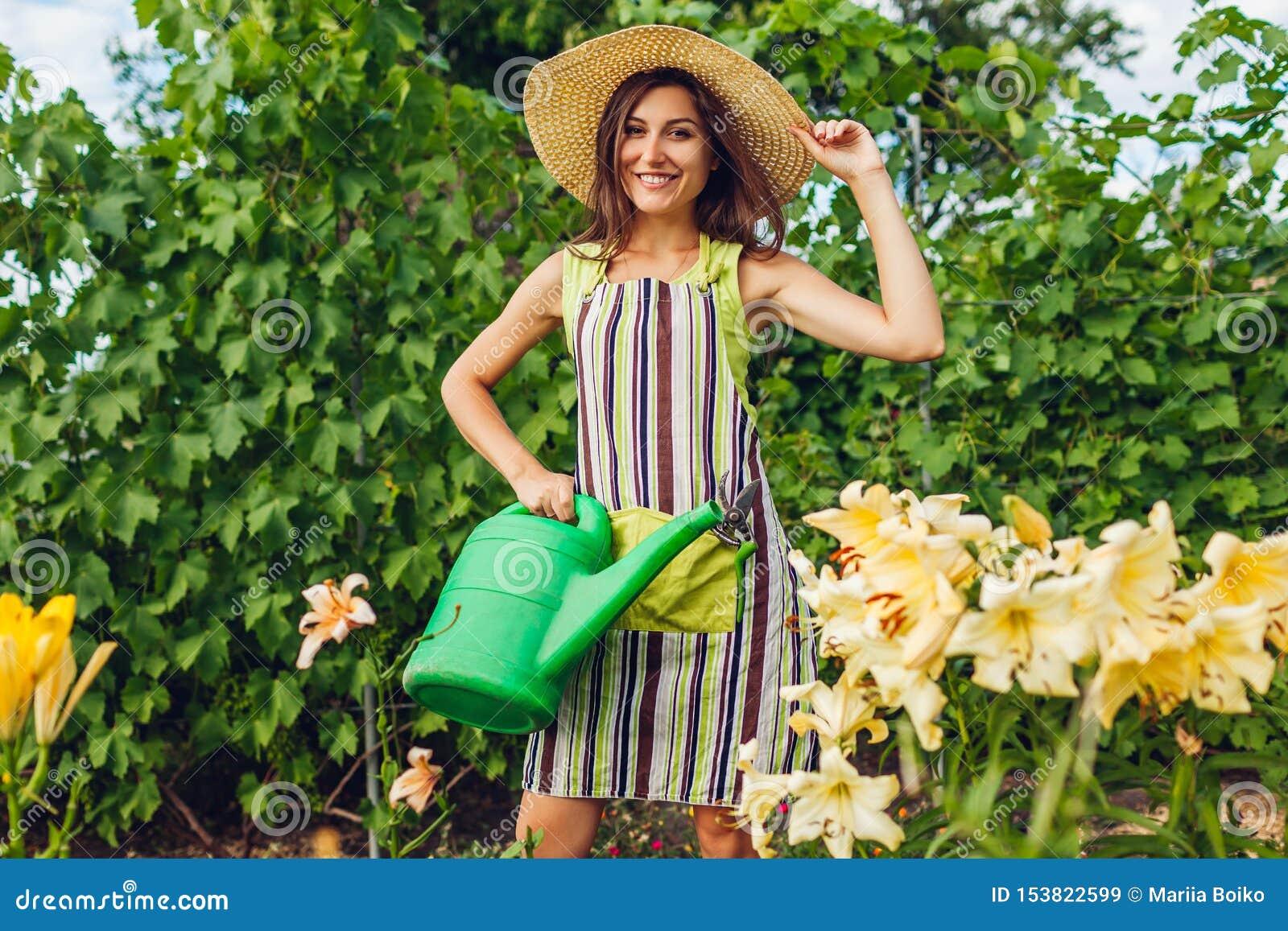 Bewässerungsblumen der jungen Frau mit Gießkanne im Garten Gärtner, der um Lilien sich kümmert Im Garten arbeitenkonzept