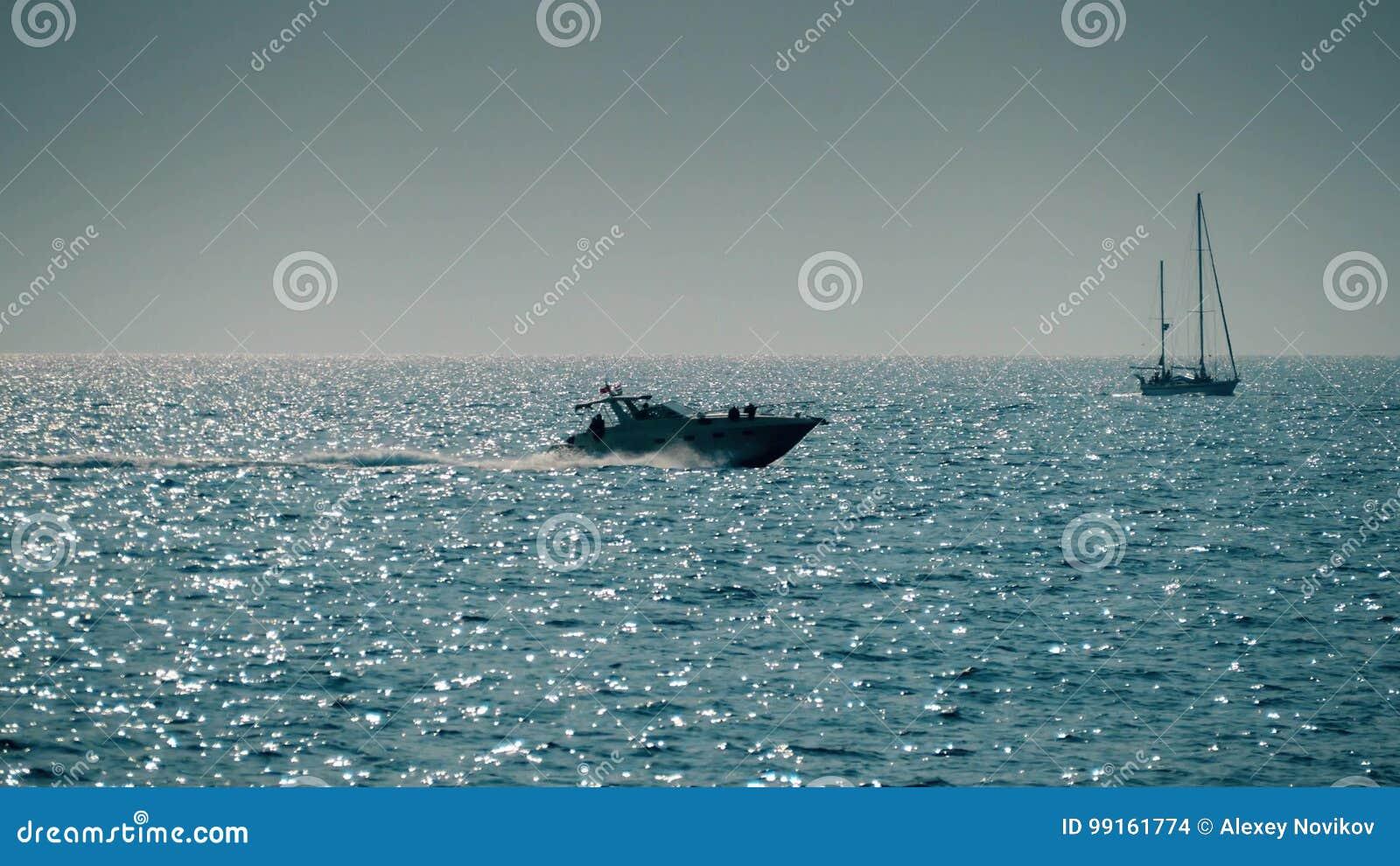Bewegende zeilboot en motorboot in het overzees