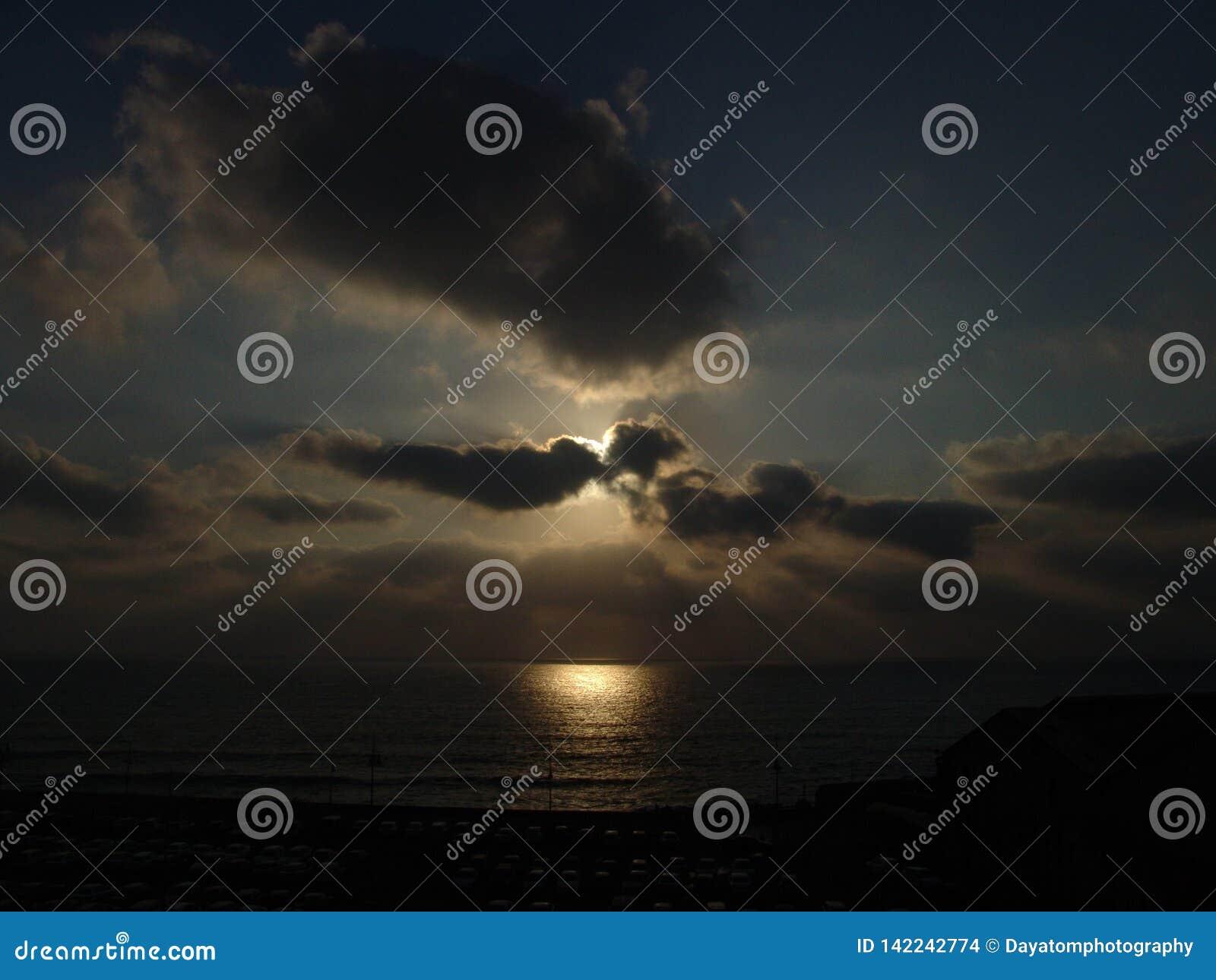 Bewolkte die zonsondergang over een strand met veel auto s op een groot parkeerterrein in dark worden geparkeerd