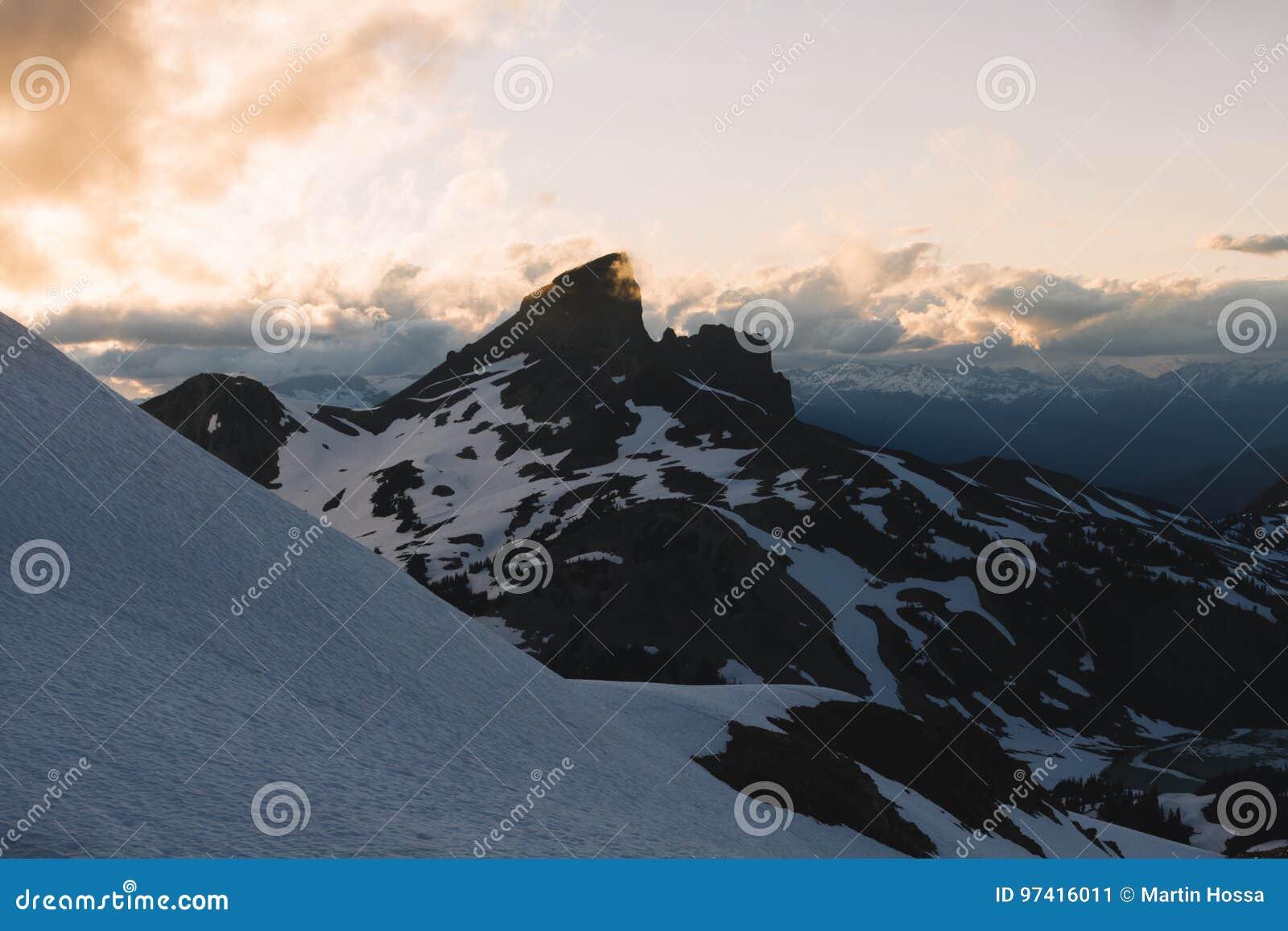 Bewolkte humeurige zonsondergang in sneeuwbergen boven Garibaldi Lake op Panoramarand