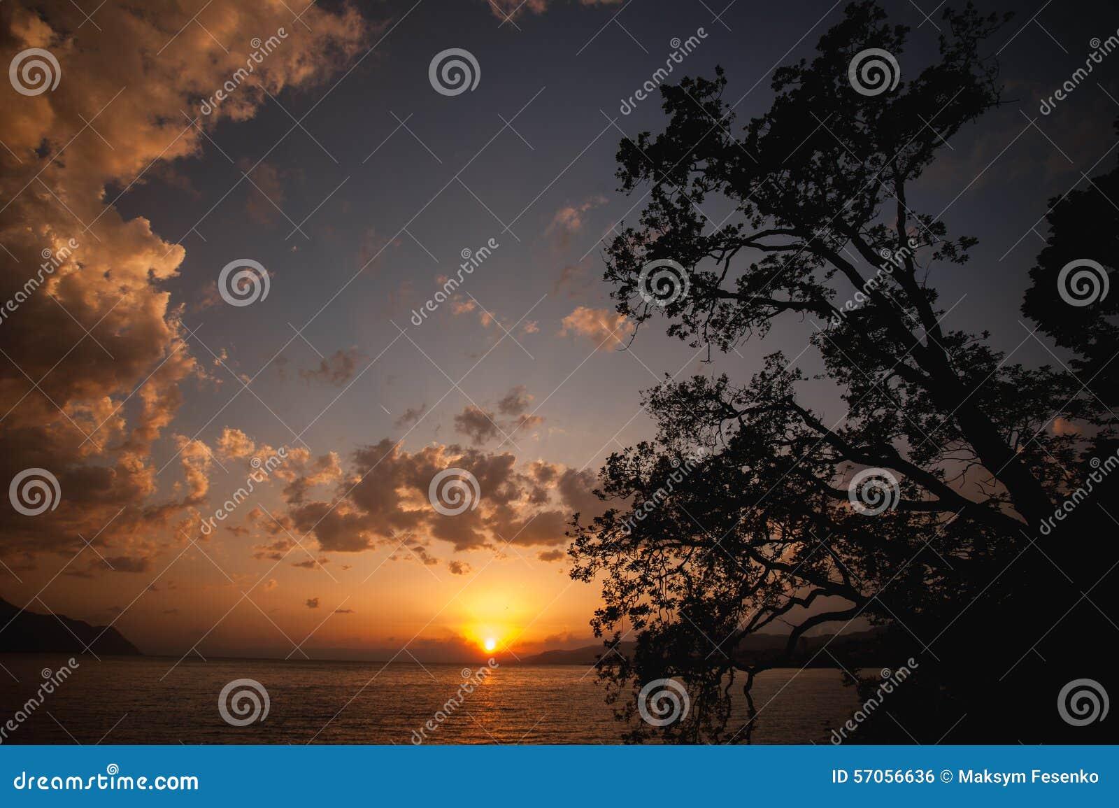 Bewolkte oranje zonsondergang over meer