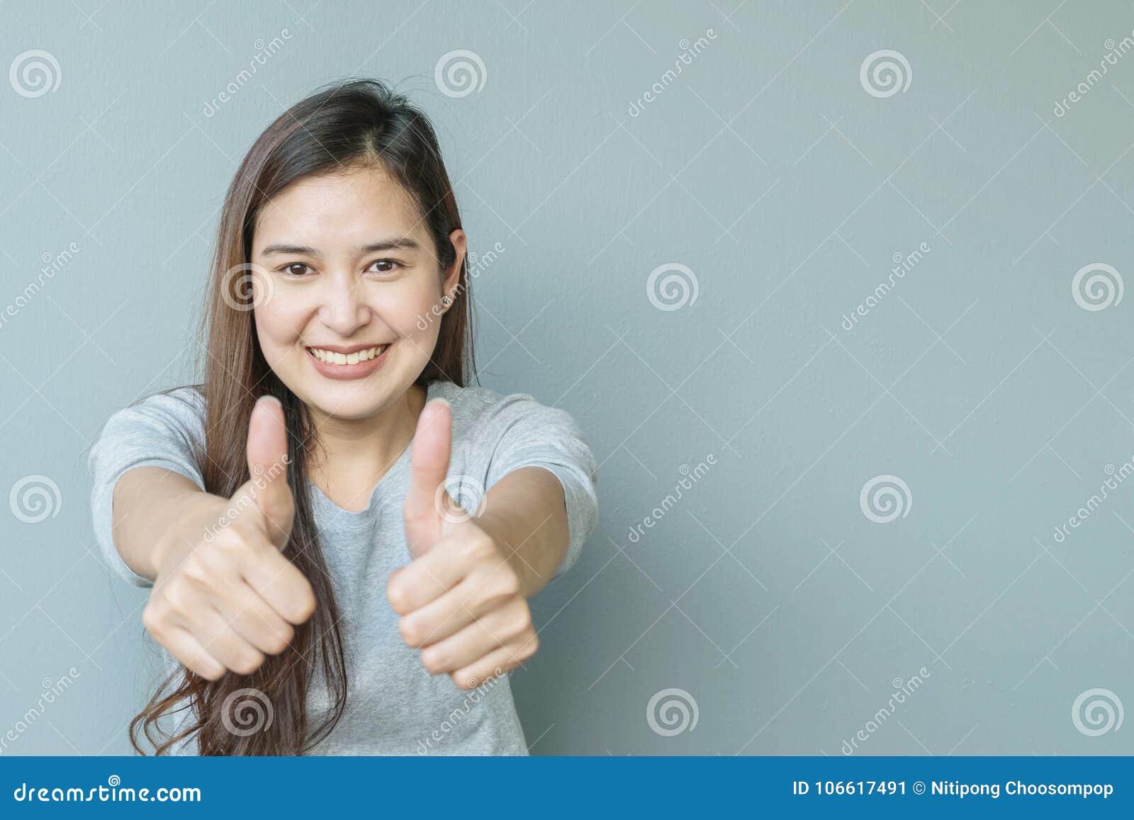 Bewondert de close-up Aziatische vrouw met motie met glimlachgezicht op de vage geweven achtergrond van de cementmuur met exempla