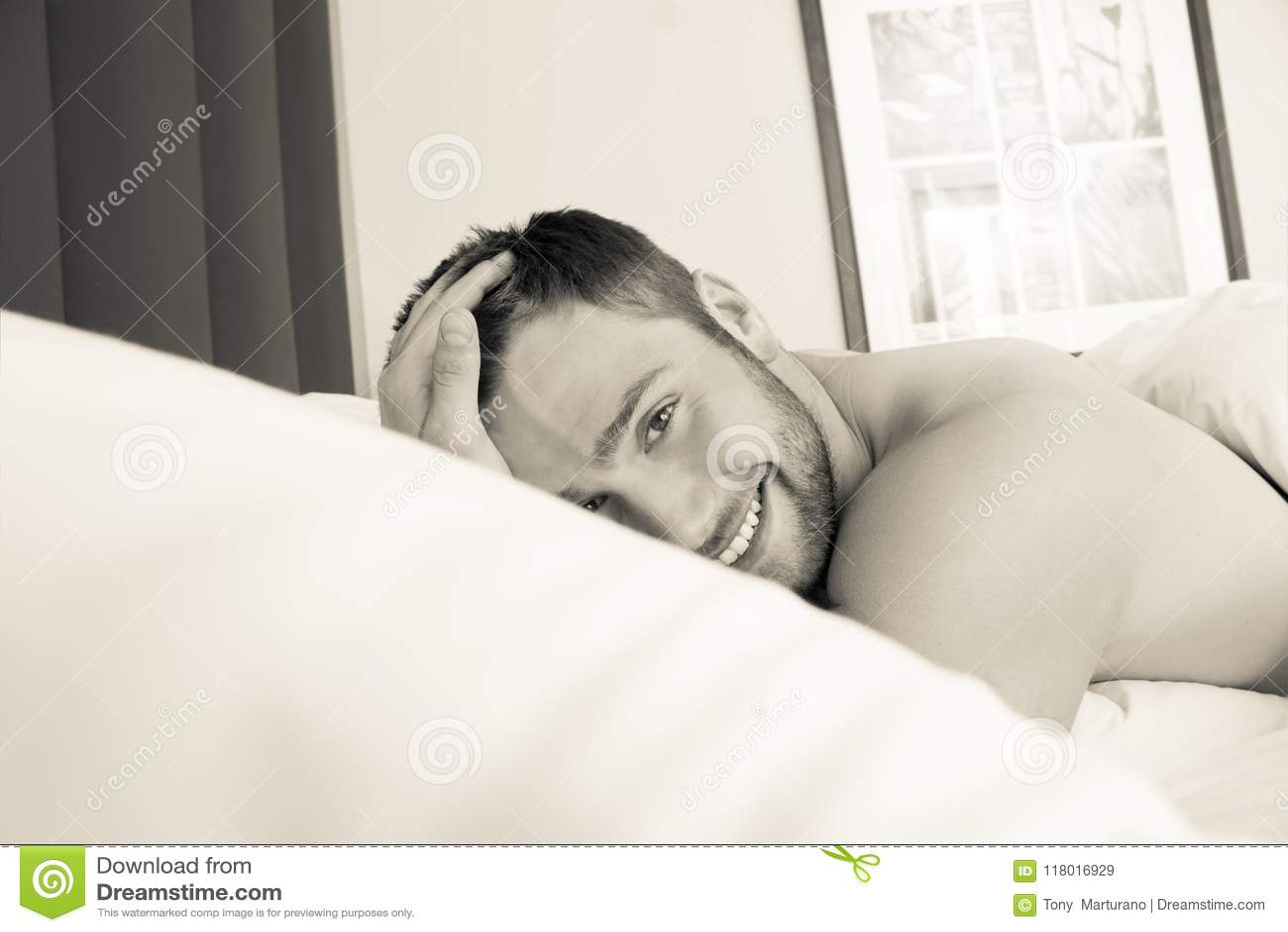 Bez koszuli seksowny hunky mężczyzna z brodą kłama nagiego w łóżku