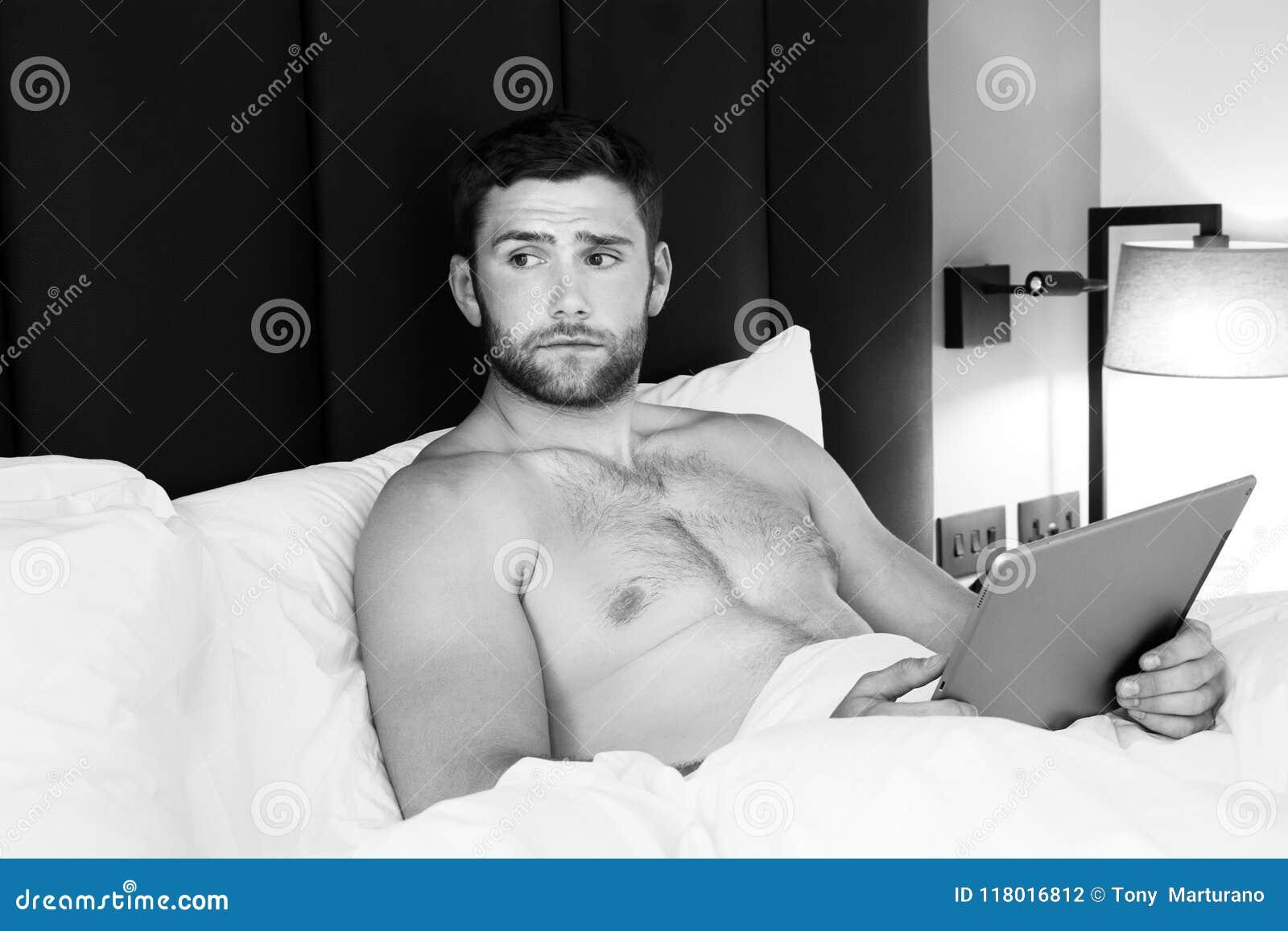 Bez koszuli seksowny hunky mężczyzna z brodą używa ipad pastylkę w łóżku