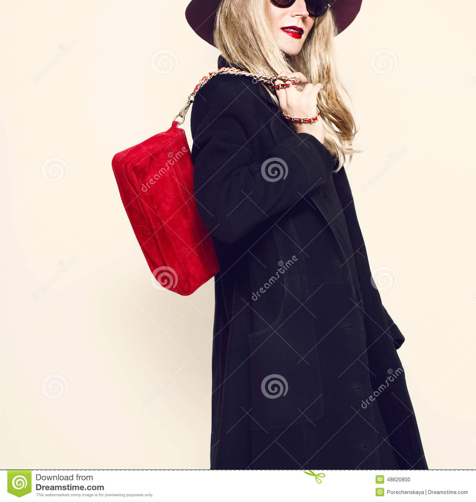 Bezaubernde Blondine im klassischen schwarzen Mantel und im roten Hut Herbst fashi