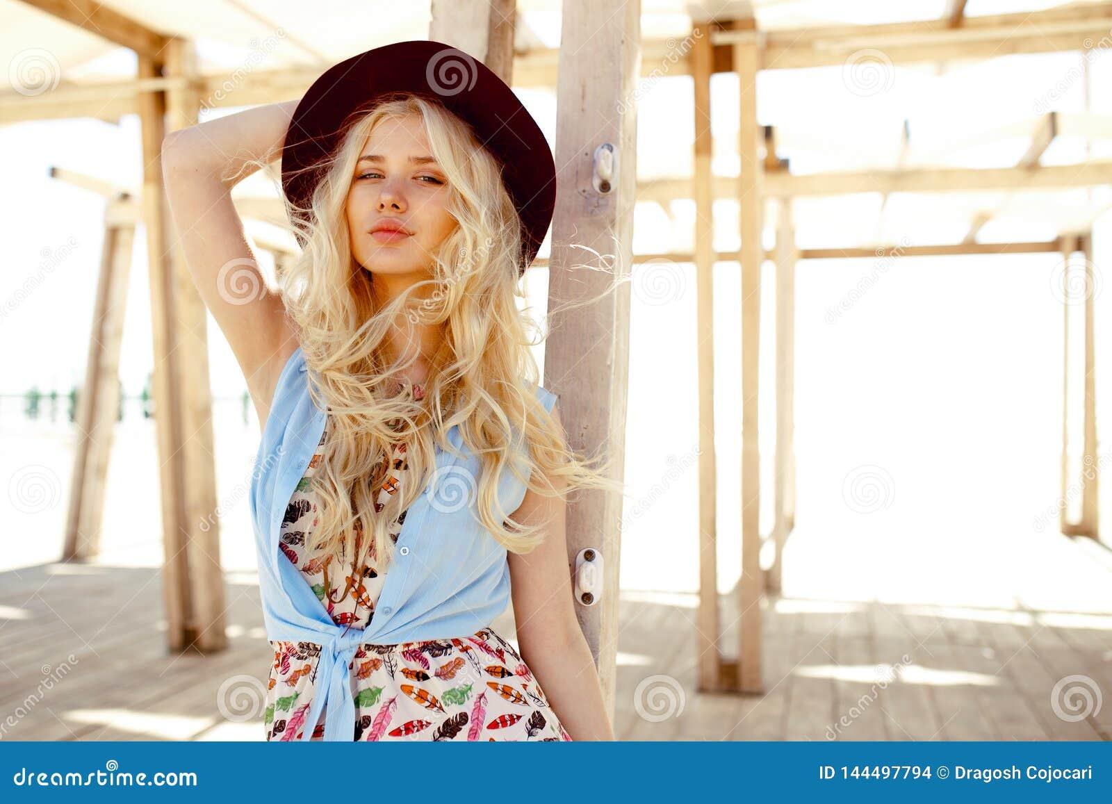 Bezaubernde Blondine mit dem gelockten Haar, den blauen Augen, große Lippen und Burgunder-Hut, lokalisiert am hölzernen errichten