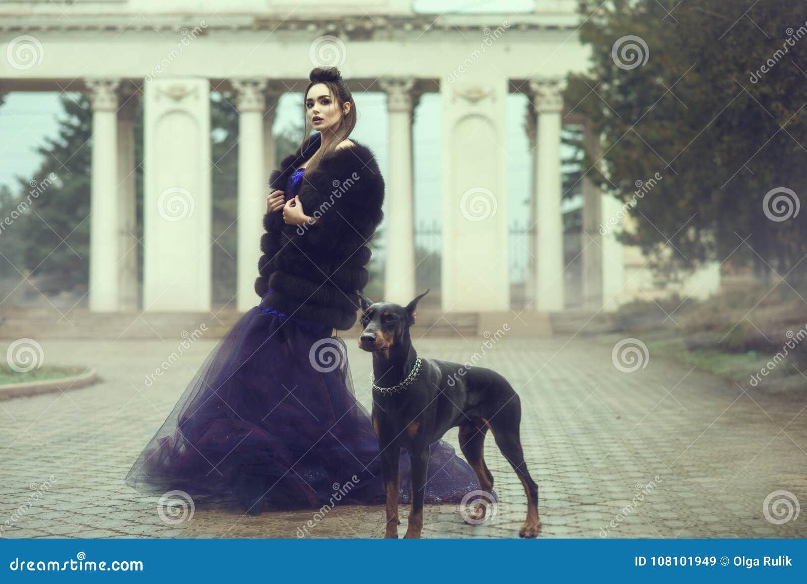 Bezaubernde Dame, die violettes Abendkleid der luxuriösen Paillette und den Pelzmantel steht auf der Gasse im Park mit ihrem Dobe