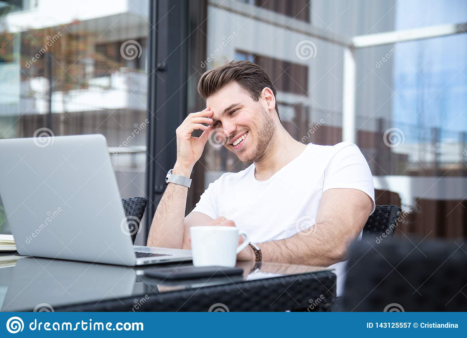 Bezaubernder junger erwachsener Mann, der an Laptop auf Morgen-Zeit im Freien arbeitet