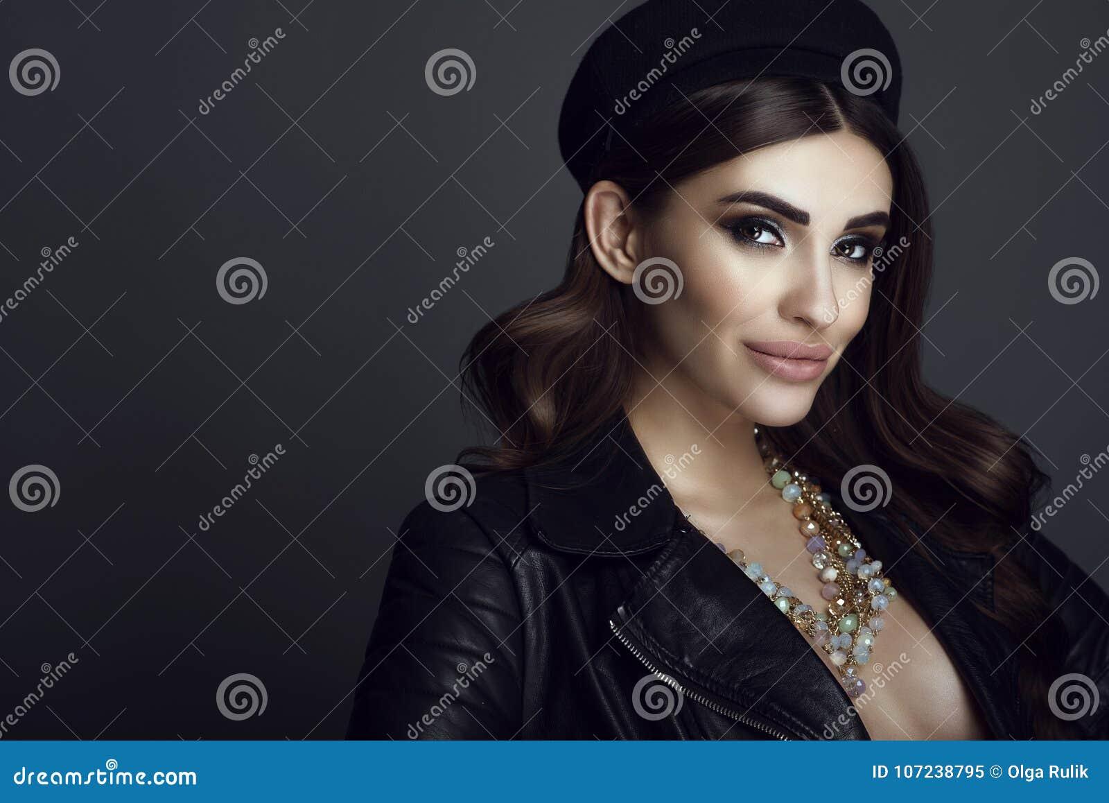 Bezauberndes dunkelhaariges Modell mit schönem bilden und das glatte Haar, das schwarzen Pillenschachtelhut, Lederjacke und Edels