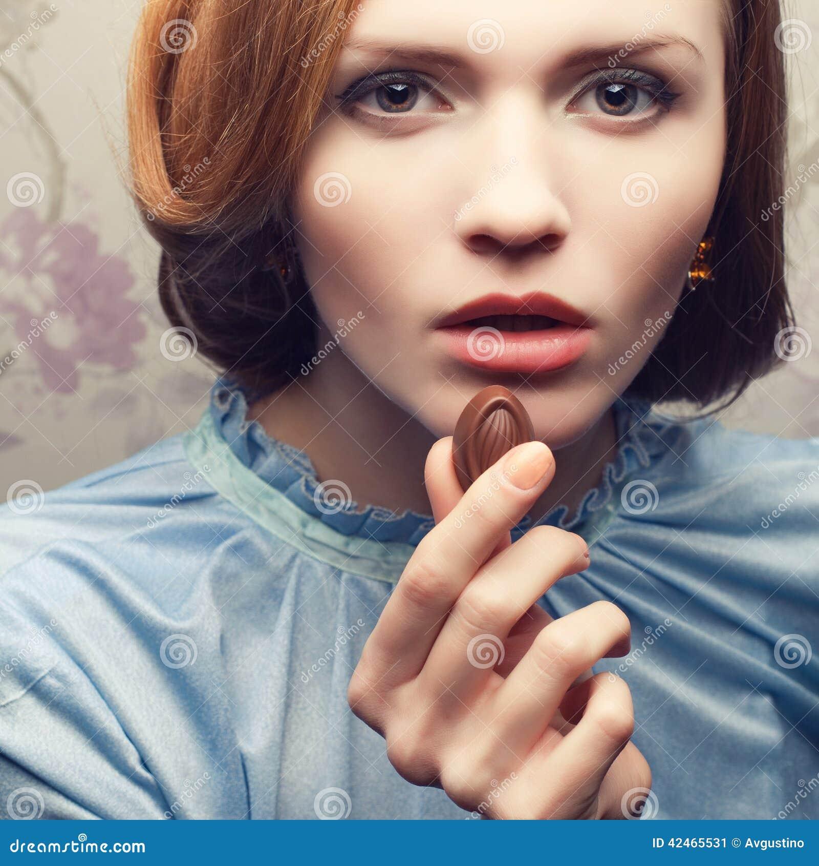 Bezauberndes rothaariges (Ingwer) Mädchen im blauen Kleid Süßigkeit essend