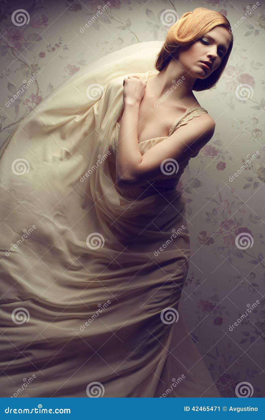 Bezauberndes rothaariges (Ingwer) Mädchen im vapory Kleid