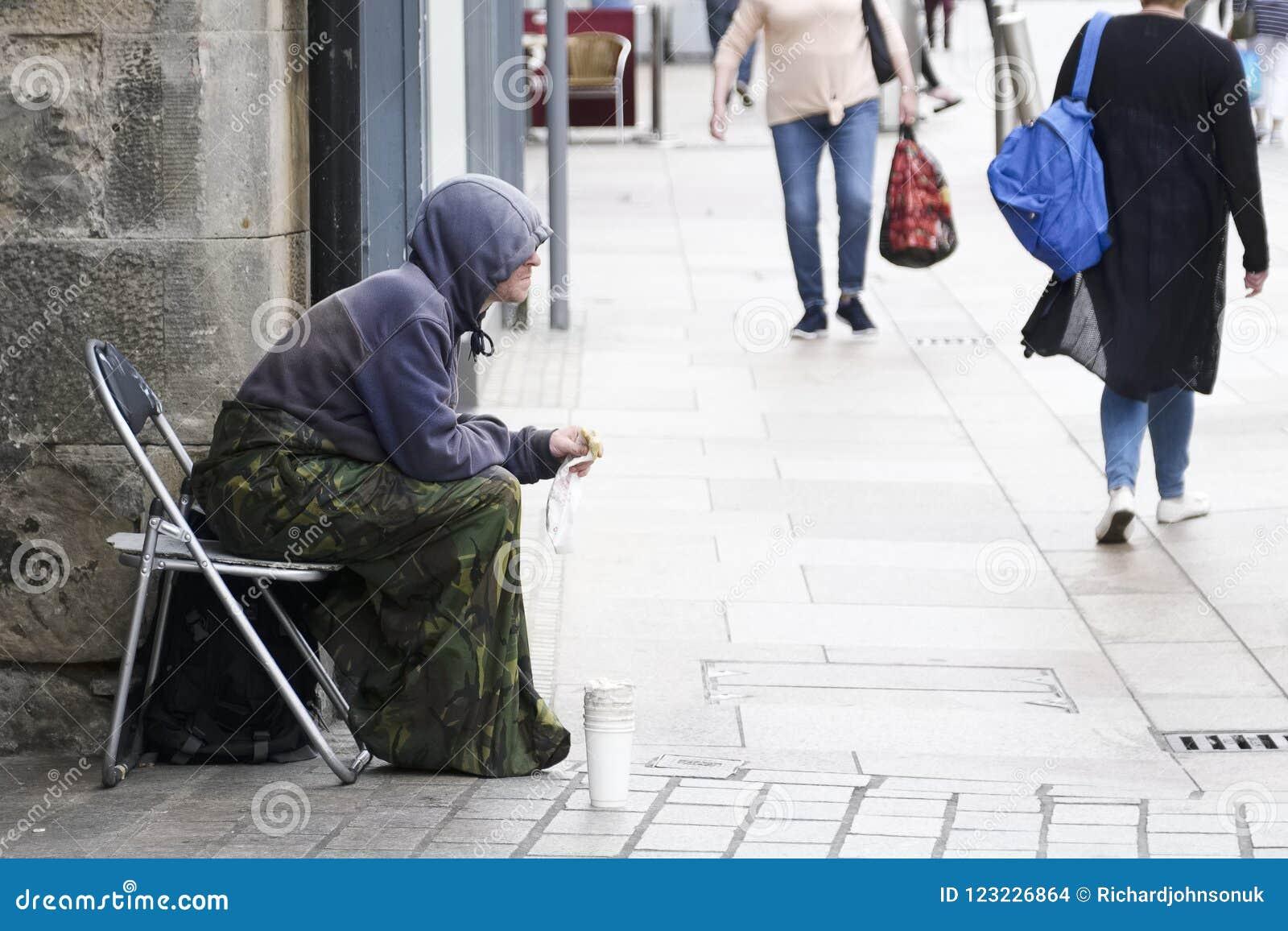 Bezdomny żebrak jest ubranym hoodie z filiżanką dla zmiany w UK z kupującymi w tle siedział na ruchliwej ulicie