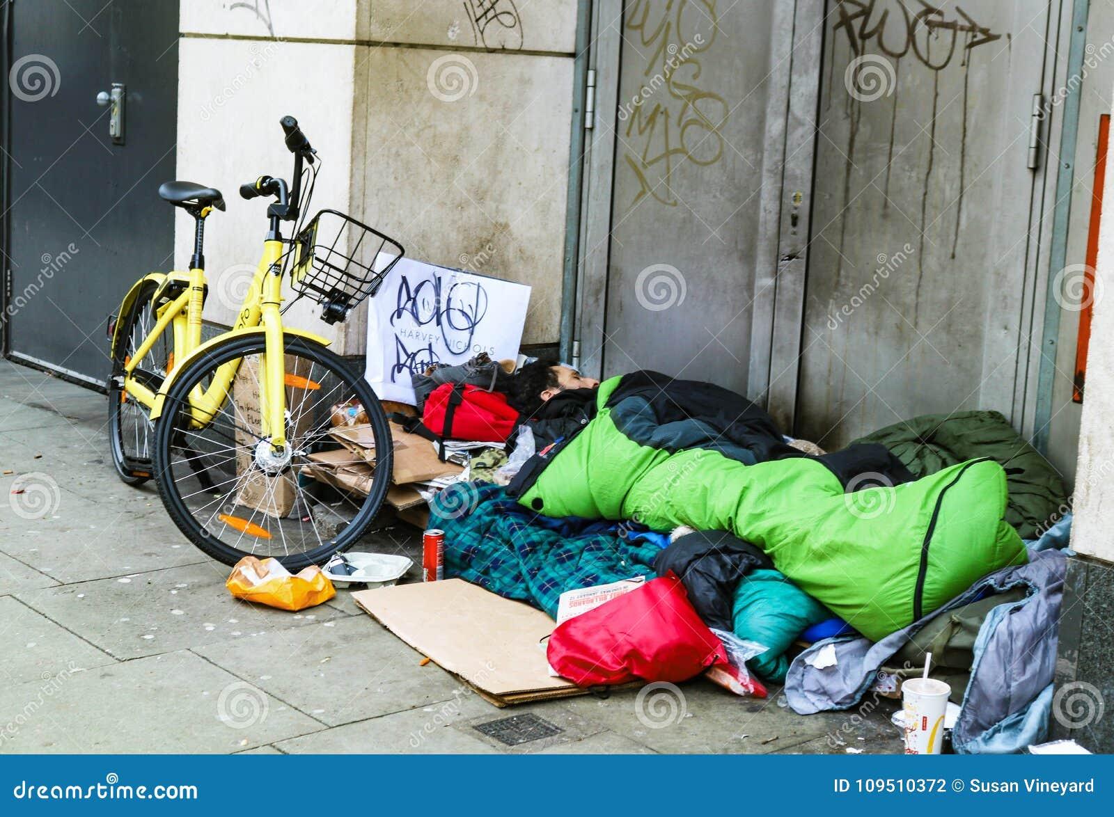 Bezdomny mężczyzna z rowerową i sypialną torbą uśpioną w drzwi w Południowym Kennsington Londyński UK 1-10-2018