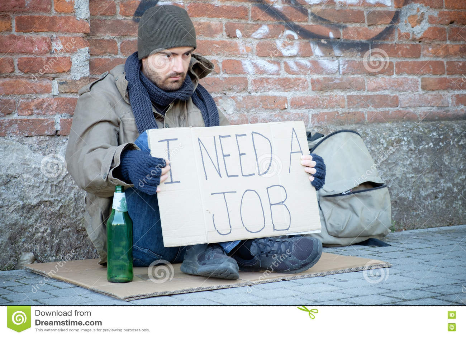 Bezdomny sadzający w ulicie i pytać dla pracy