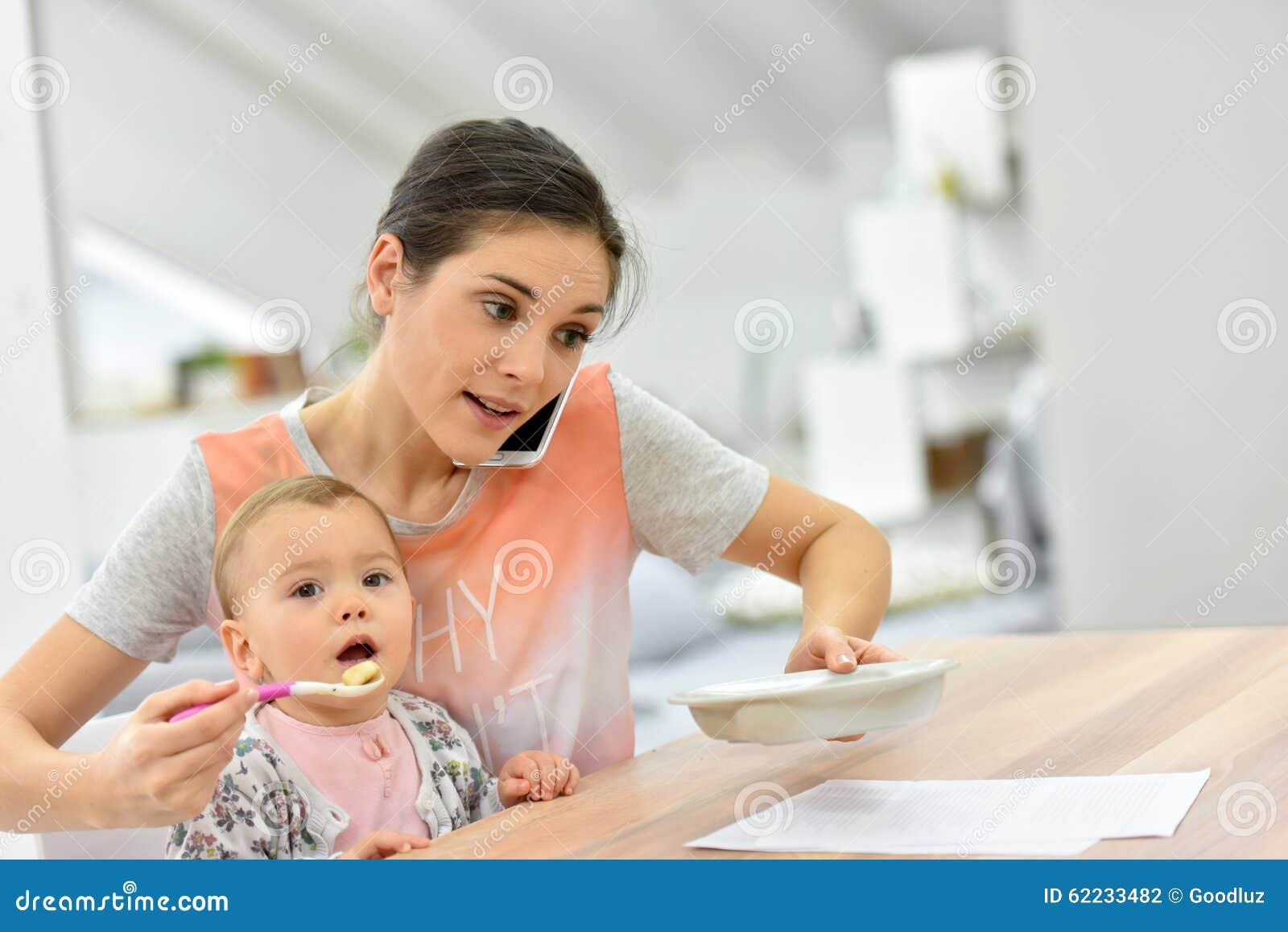 Bezige moeder voedende baby en het spreken op de telefoon