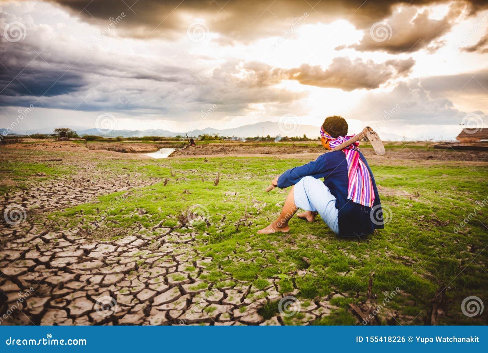 Beznadziejny Średniorolny obsiadanie na suchej ziemi z motyką obok on Globalne ocieplenie kryzys,