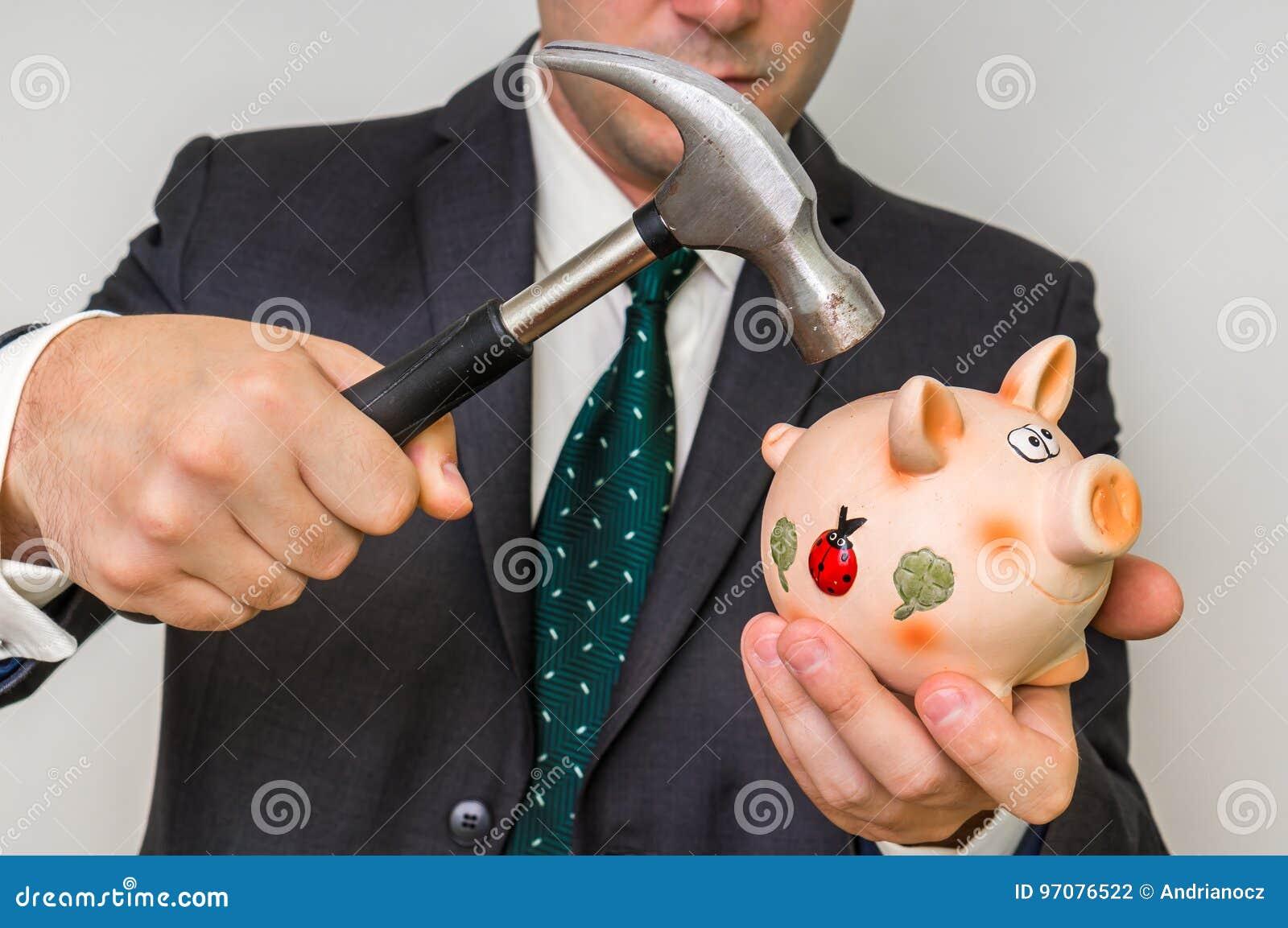 Beznadziejny biznesmena łamania prosiątka bank z młotem