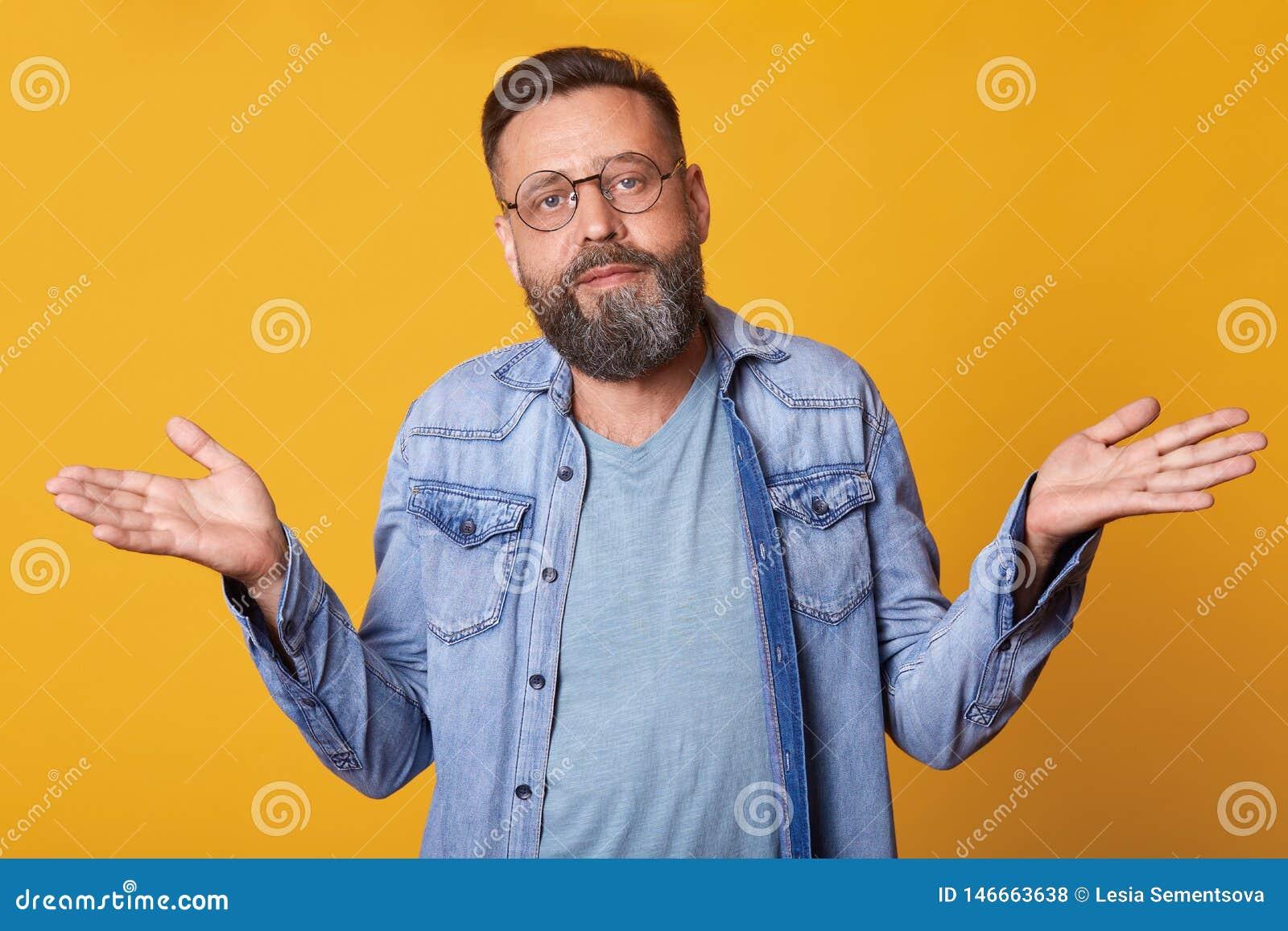 Beznadziejny desperacki w średnim wieku mężczyzna jest ubranym błękitną przypadkową t koszula, cajg kurtkę i modnych round widowi