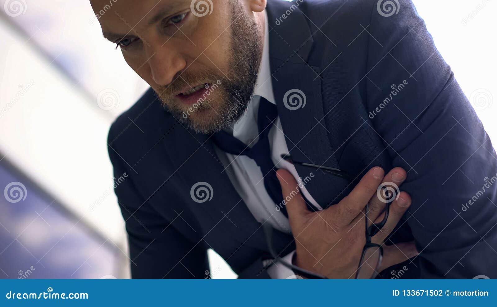 Bezorgde bedrijfsmens die borstpijn, overwerkte manager, hartaanval voelen