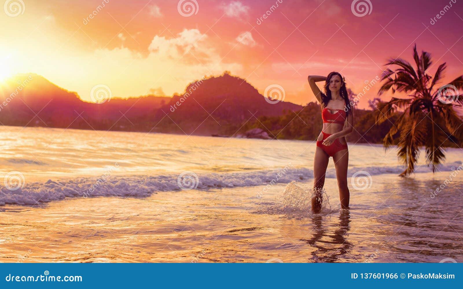 Bezpłatna kobieta Cieszy się oceanu popiół przy zmierzchem