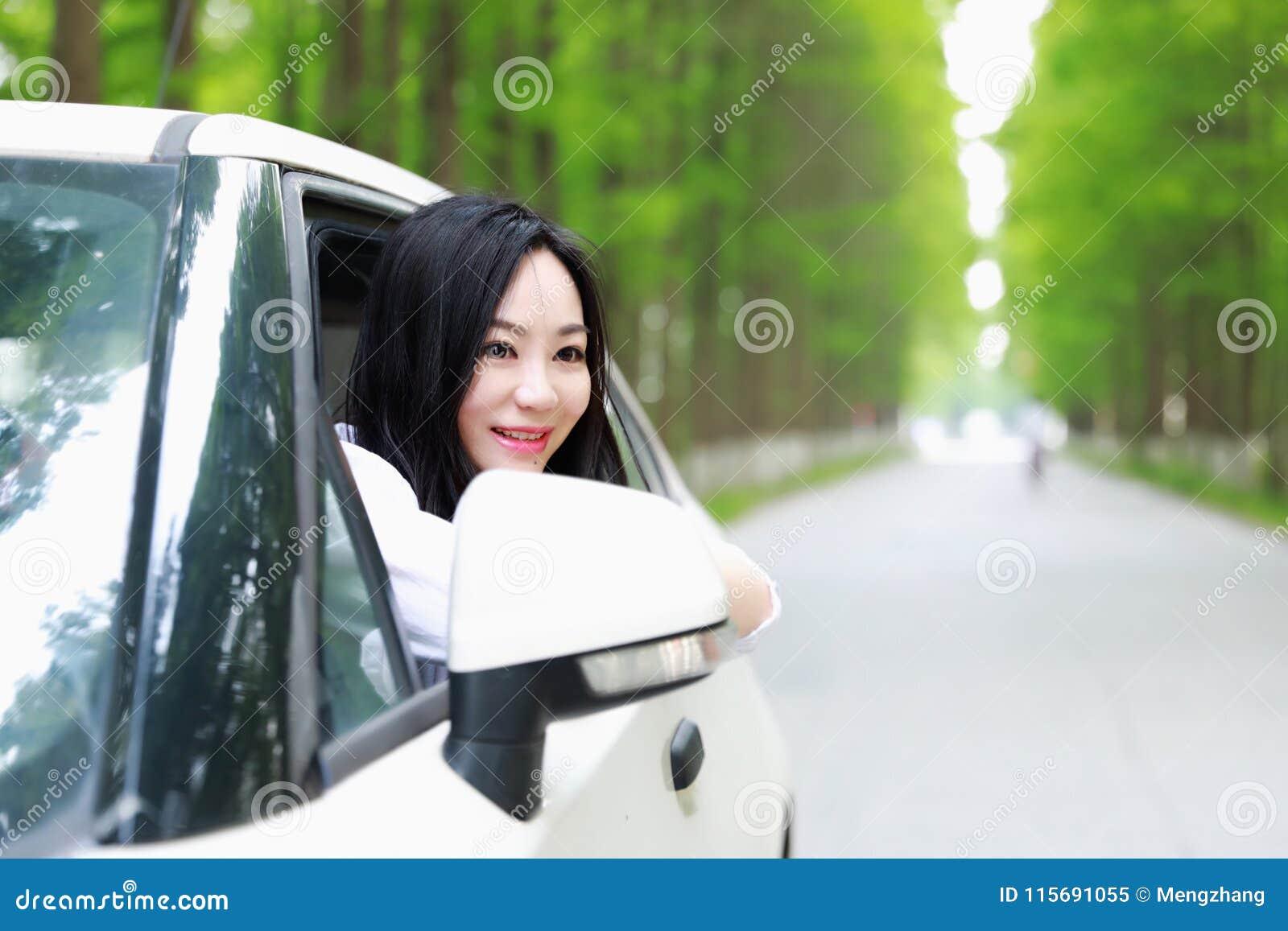 Bezpłatny niestaranny causual piękno siedzi na białym samochodowym parking na lasowej drodze w lato naturze plenerowej